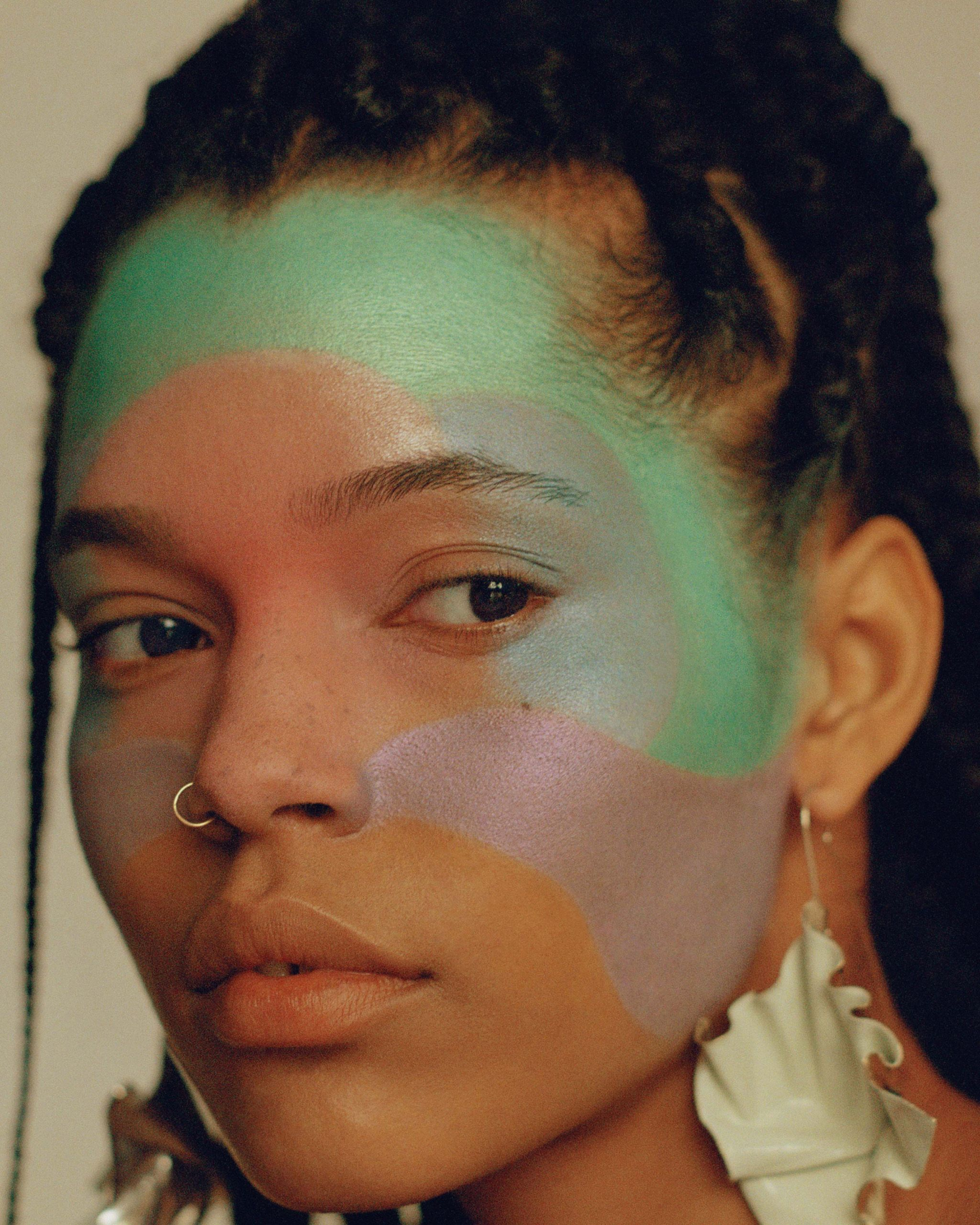 close up portrait black model with purple and green make up for vogue arabia