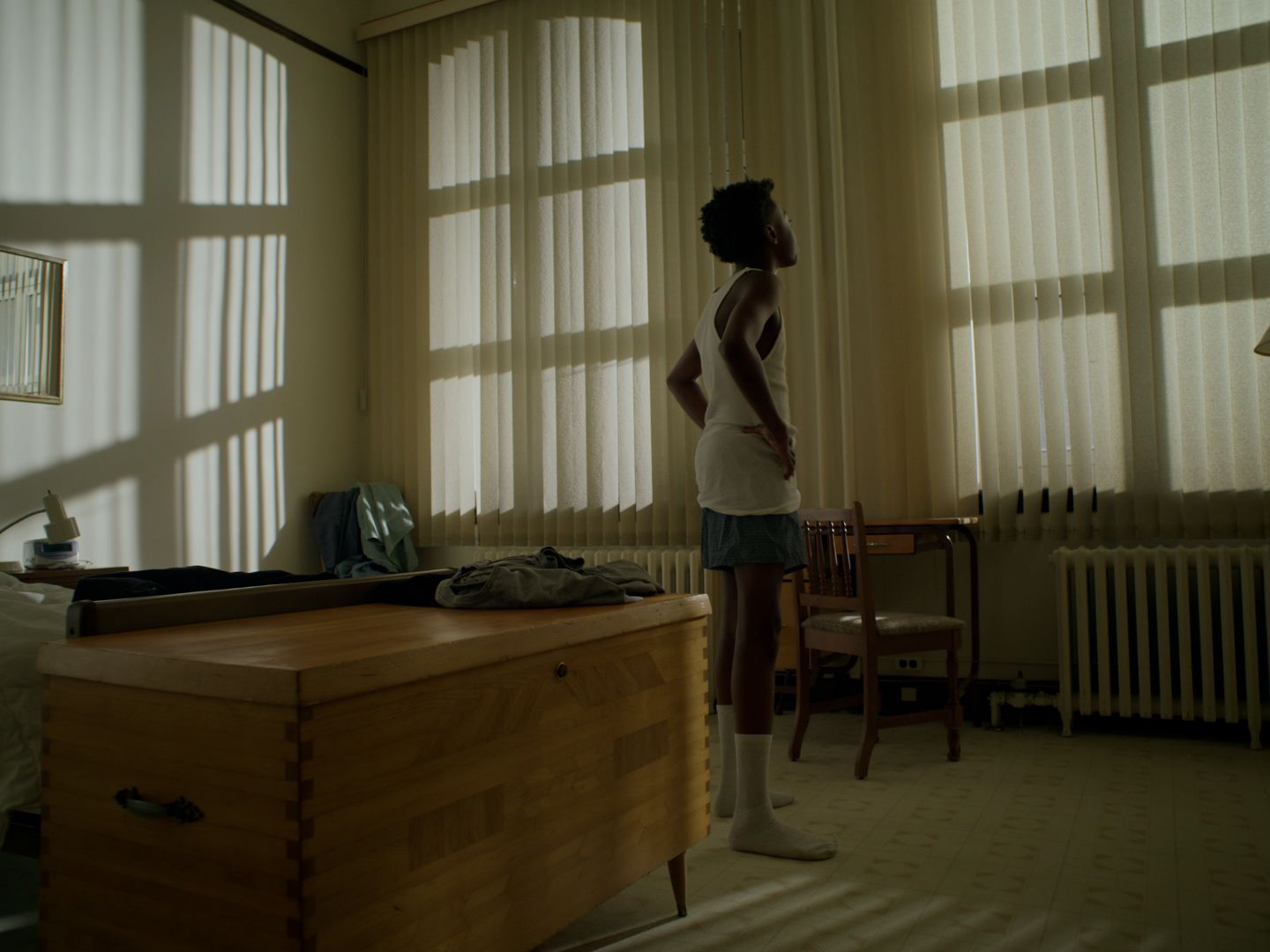 Young boy standing in his boxer shorts with a camisole and his socks. He is in a vintage looking room and looking through the window blind.