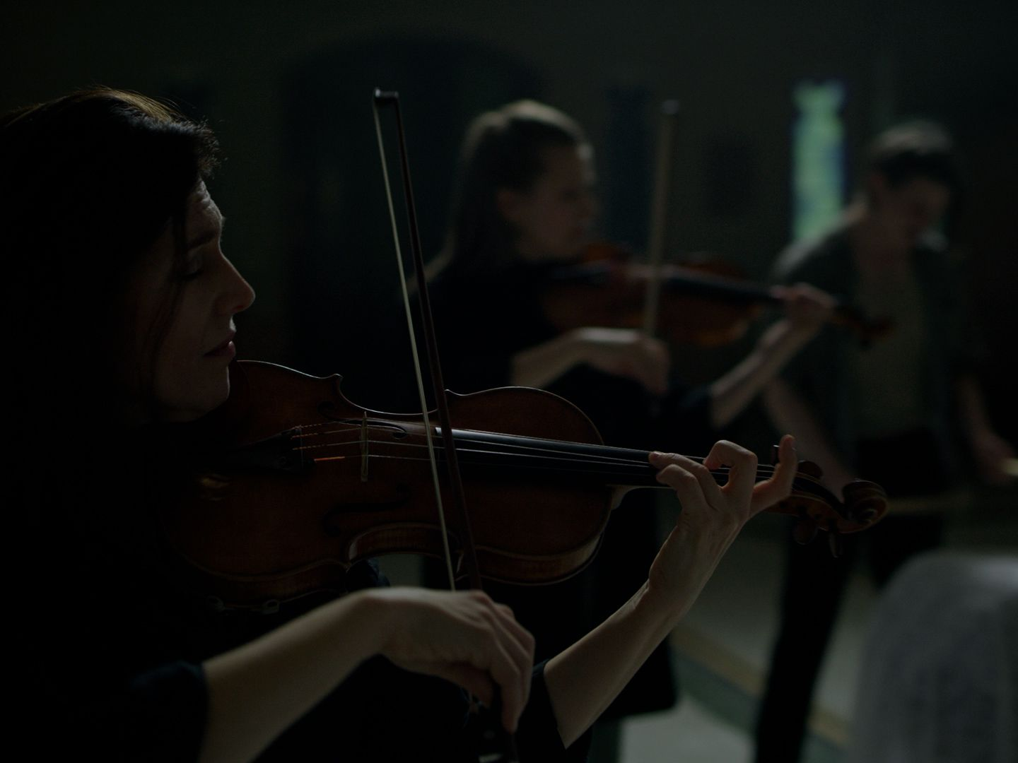 Two women are playing violin in a dark room, there is a third musician on the right.