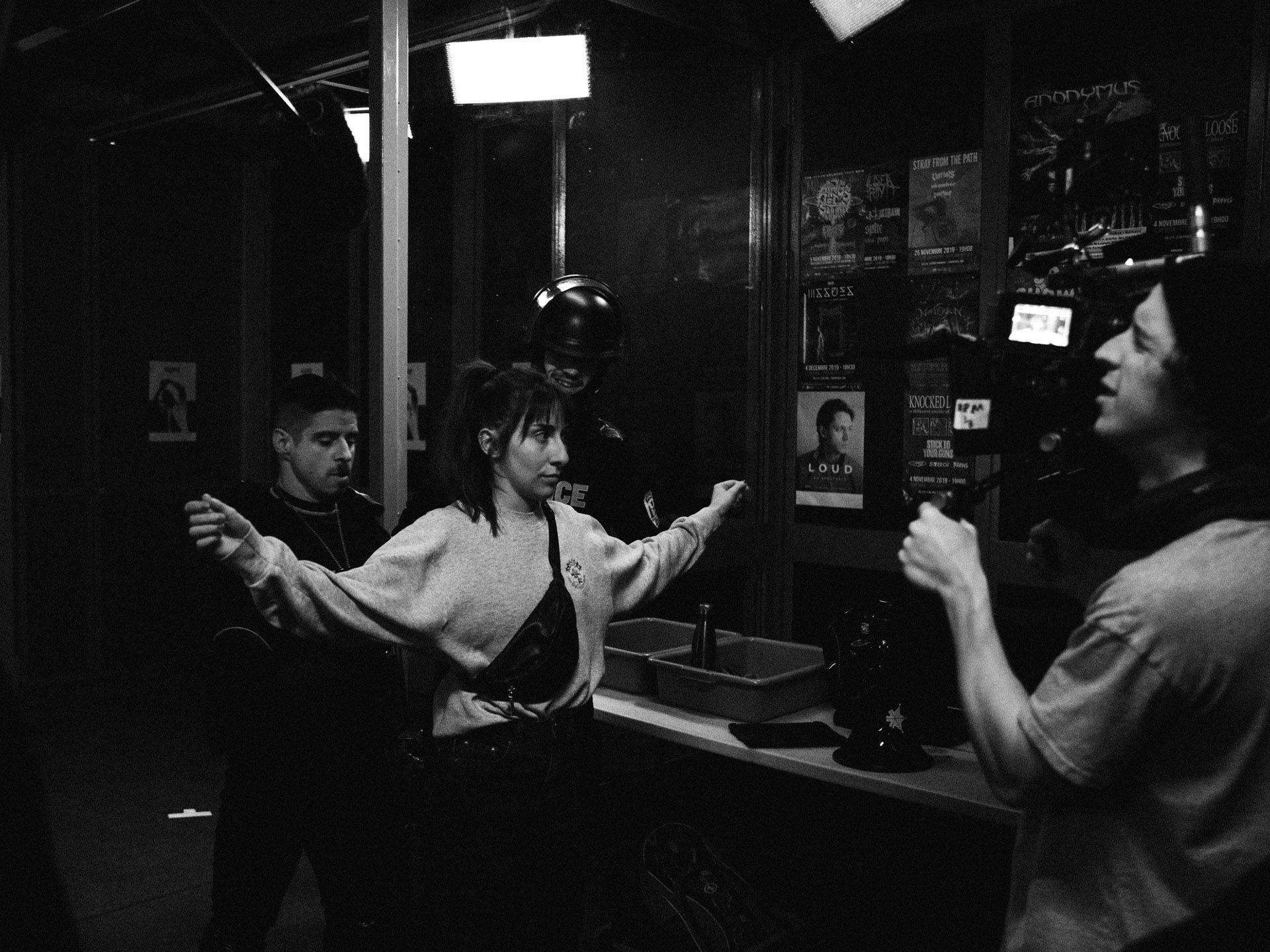 actors Hugolin Chevrette-Landesque and Emile Schneider dressed as cops checking pockets of woman in behind the scenes for TV series La Loi C'est La Loi filmed by Les Gamins for TV5 Unis