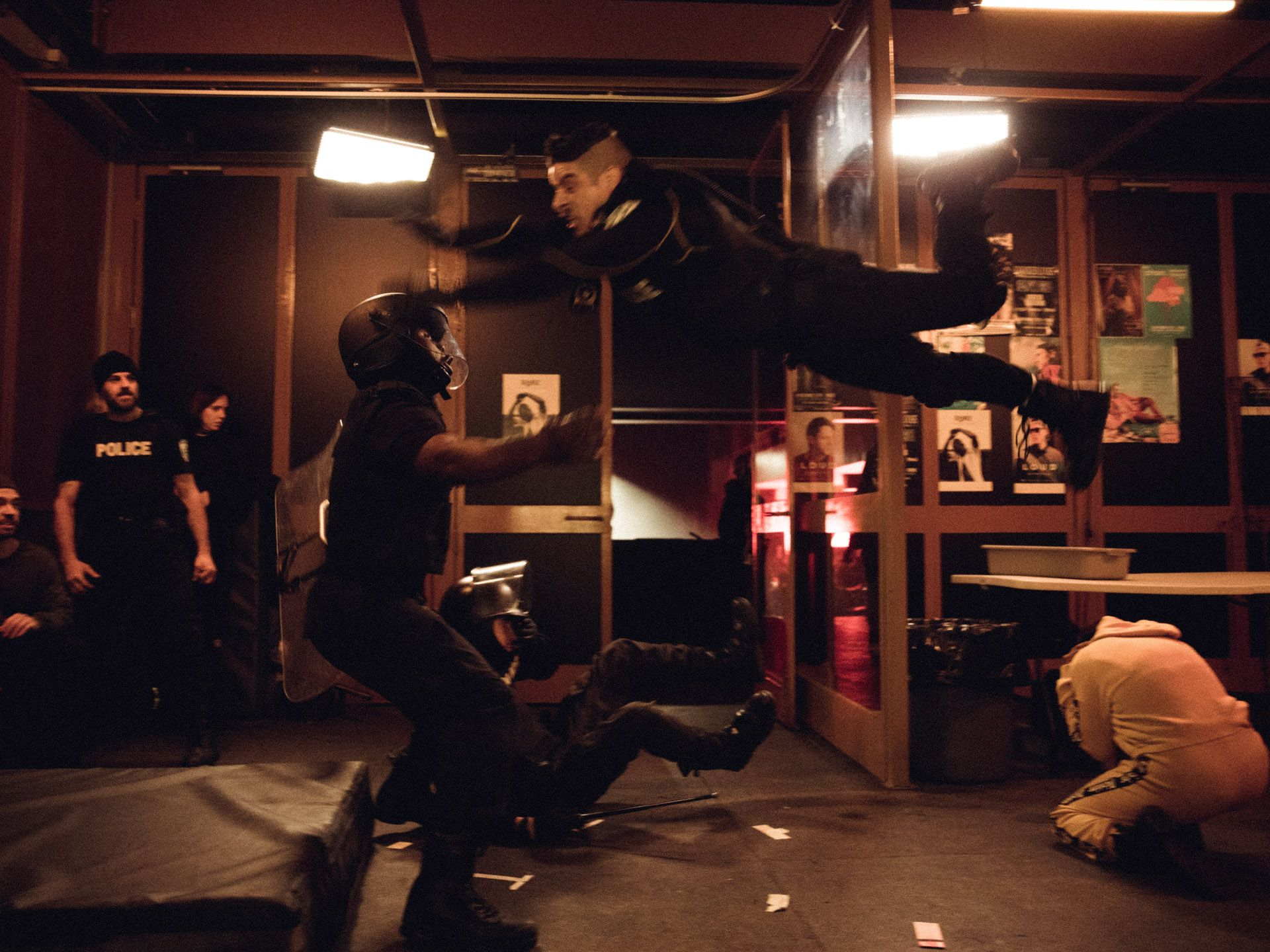 actor Hugolin Chevrette-Landesque dressed as cop jumping into the air onto another actor with safety mat behind them in behind the scenes of TV series La Loi C'est La Loi filmed by Les Gamins for TV5 Unis