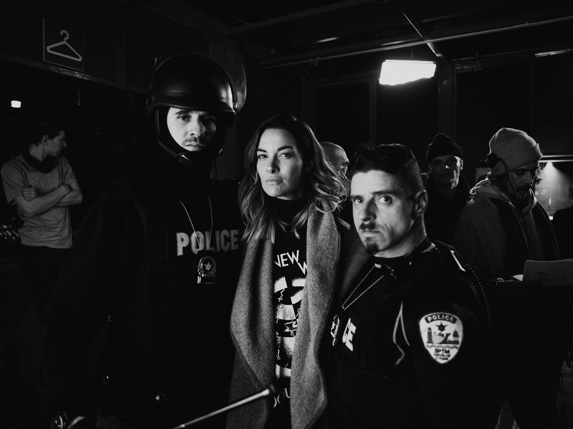 actors Hugolin Chevrette-Landesque and Emile Schneider dressed as cops posing with woman in between them in behind the scenes for TV series La Loi C'est La Loi filmed by Les Gamins for TV5 Unis