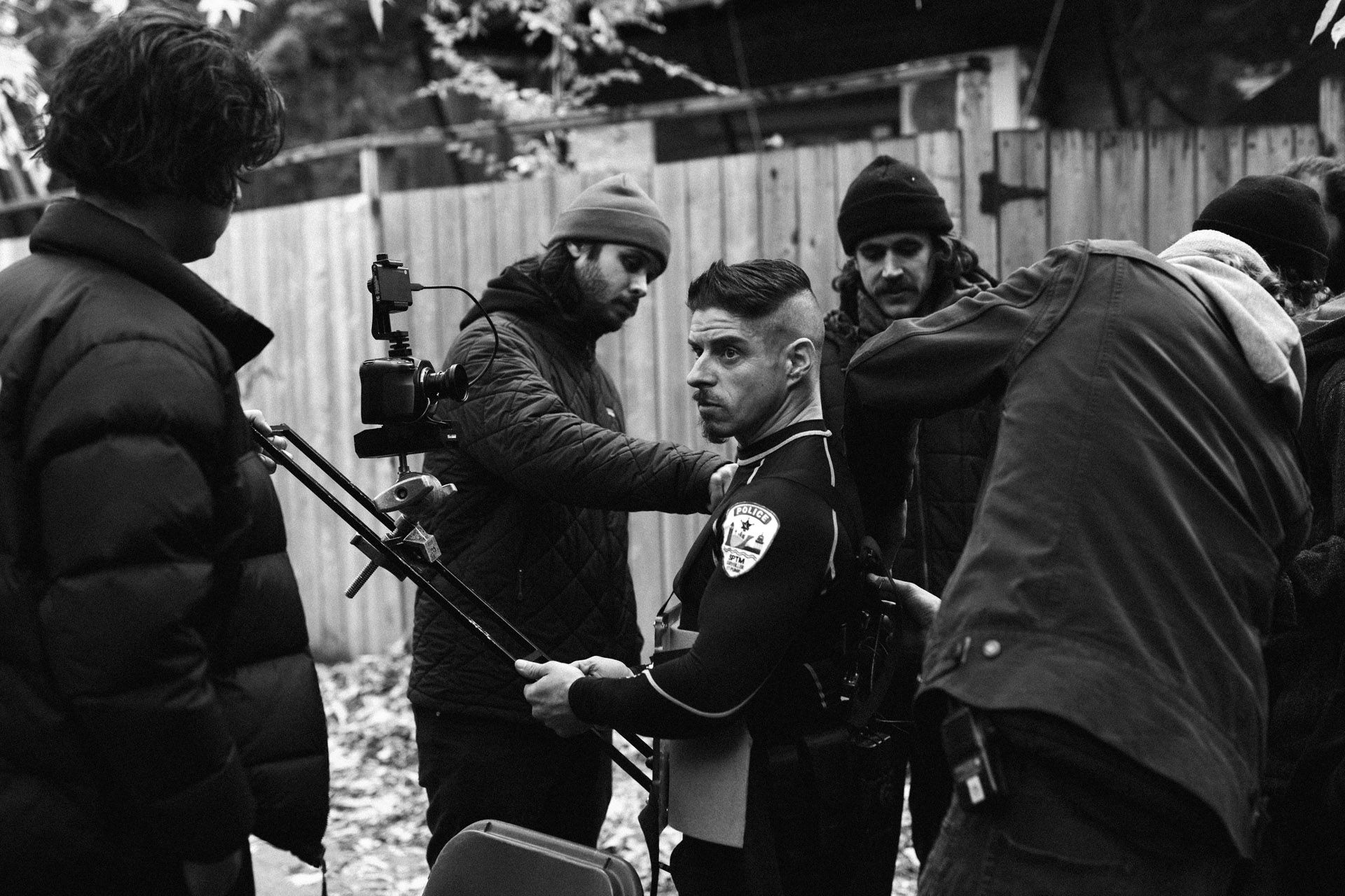 actor Hugolin Chevrette-Landesque dressed as cop getting camera harnessed on him by shooting team in behind the scenes of TV series La Loi C'est La Loi filmed by Les Gamins for TV5 Unis