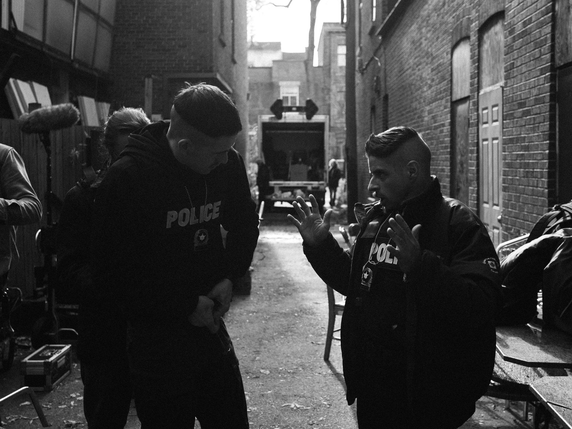 actors Hugolin Chevrette-Landesque and Emile Schneider dressed as cops talking in alley in behind the scenes for TV series La Loi C'est La Loi filmed by Les Gamins for TV5 Unis