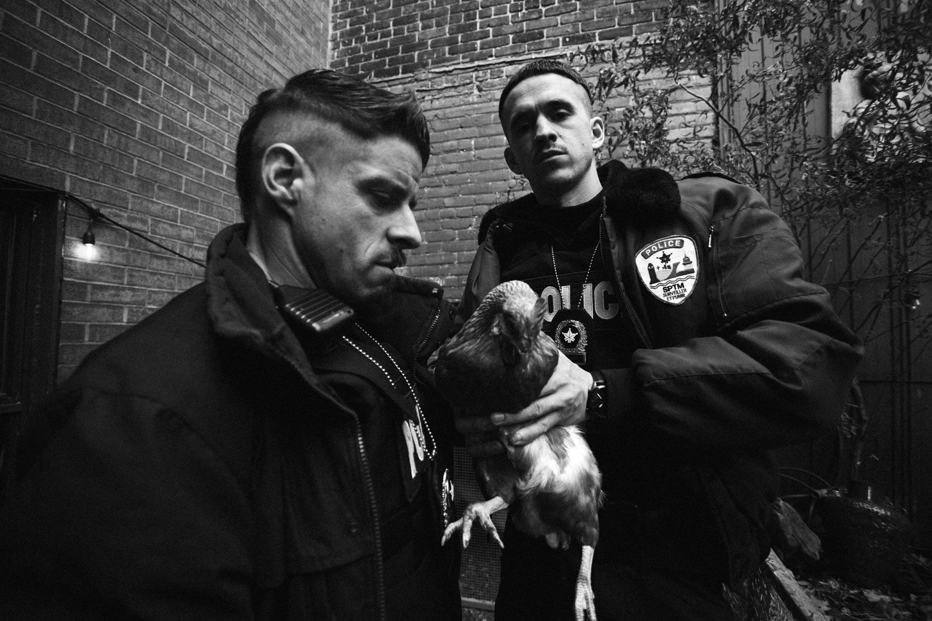 actors Hugolin Chevrette-Landesque and Emile Schneider dressed as cops holding a chicken trying to look badass in behind the scenes for TV series La Loi C'est La Loi filmed by Les Gamins for TV5 Unis