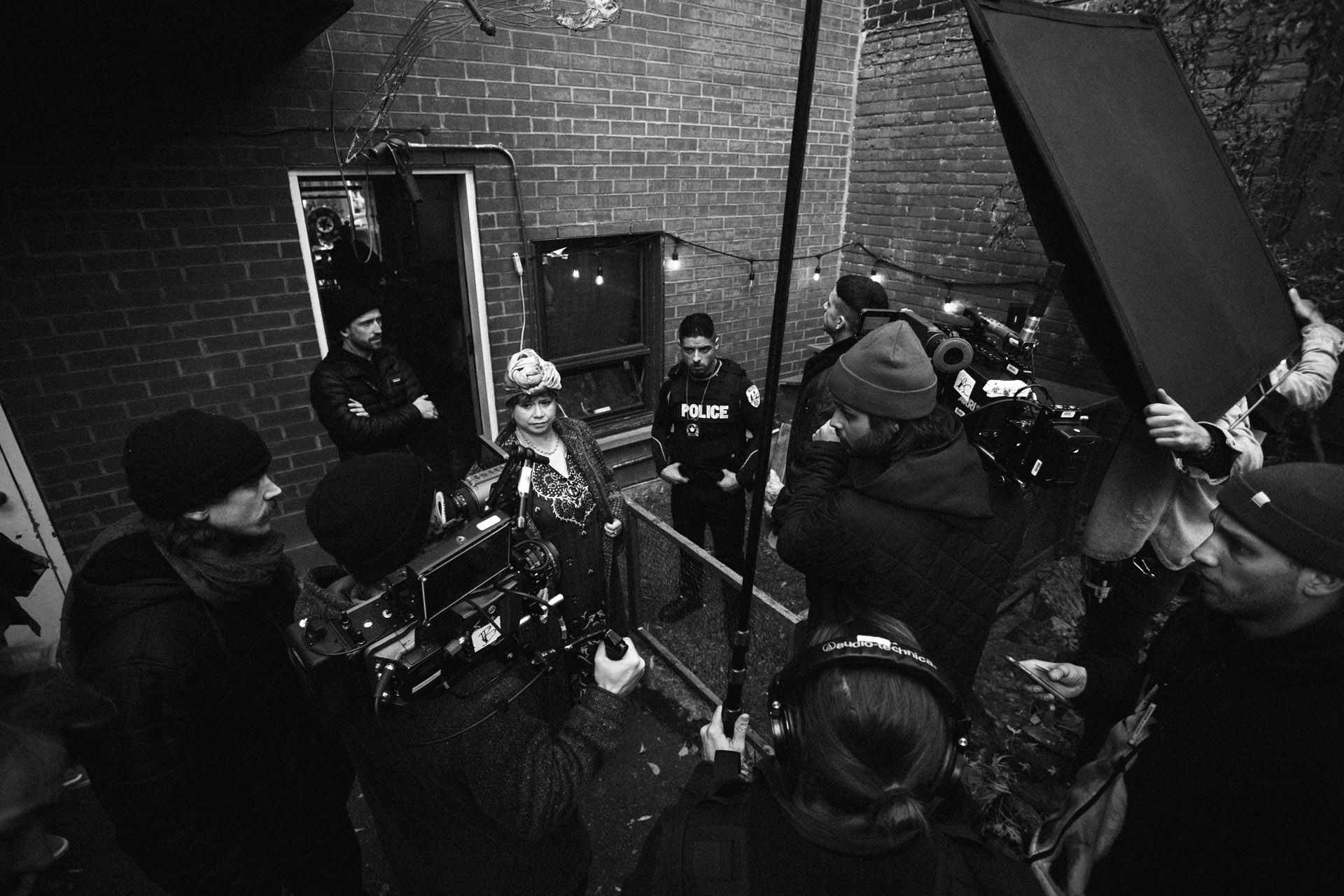 top view of shooting team with many cameras directed on actors Hugolin Chevrette-Landesque and Emile Schneider dressed as cops standing in chicken coop in behind the scenes for TV series La Loi C'est La Loi filmed by Les Gamins for TV5 Unis