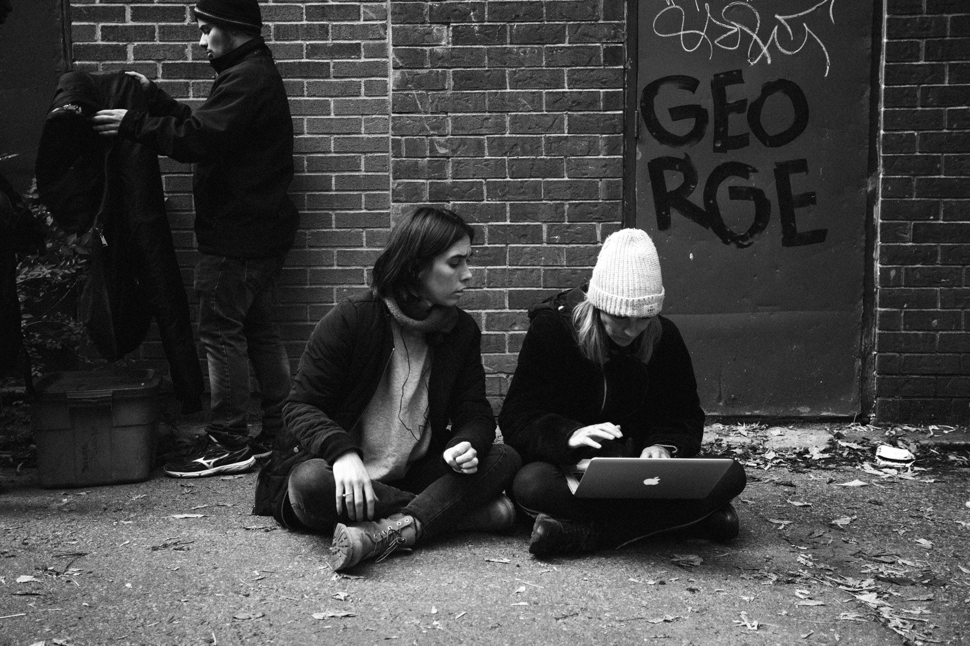 two women sitting on the ground in alley checking footage on computer in behind the scenes for TV series La Loi C'est La Loi filmed by Les Gamins for TV5 Unis