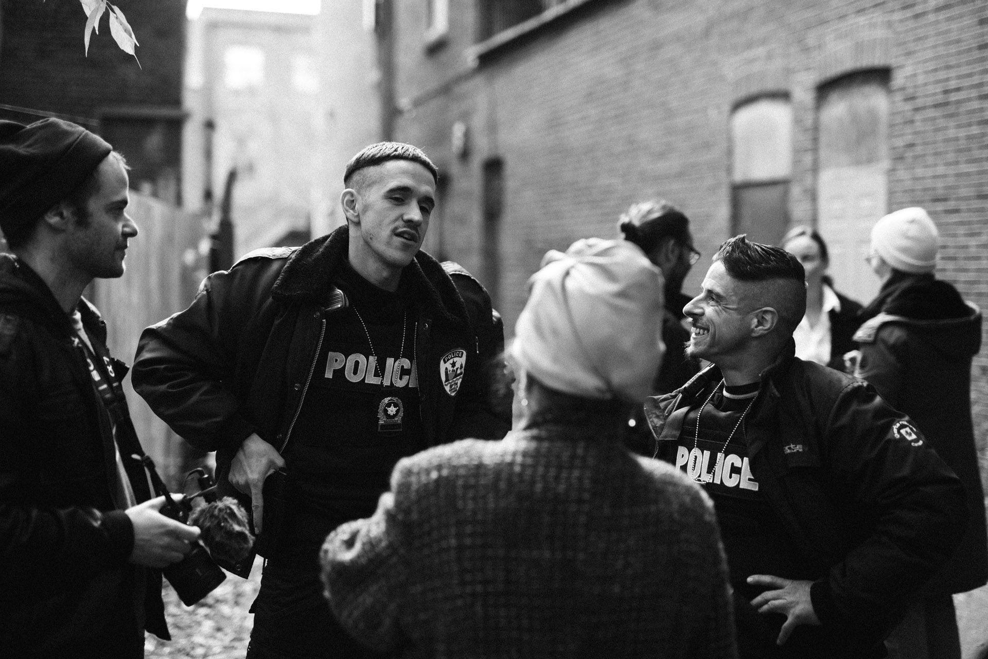 actors Hugolin Chevrette-Landesque and Emile Schneider dressed as cops talking and laughing with the filming team in behind the scenes for TV series La Loi C'est La Loi filmed by Les Gamins for TV5 Unis
