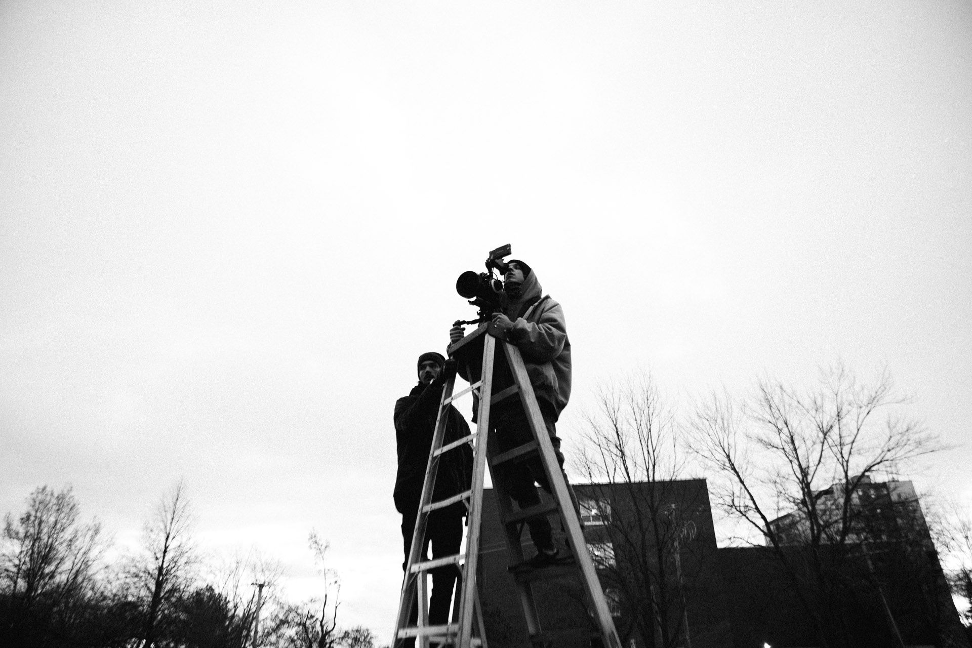 Vincent Ruel-Cote from Les Gamins up on a ladder with camera assistant to film a top view in behind the scenes filming TV series La Loi C'est La Loi at night with TV5 Unis