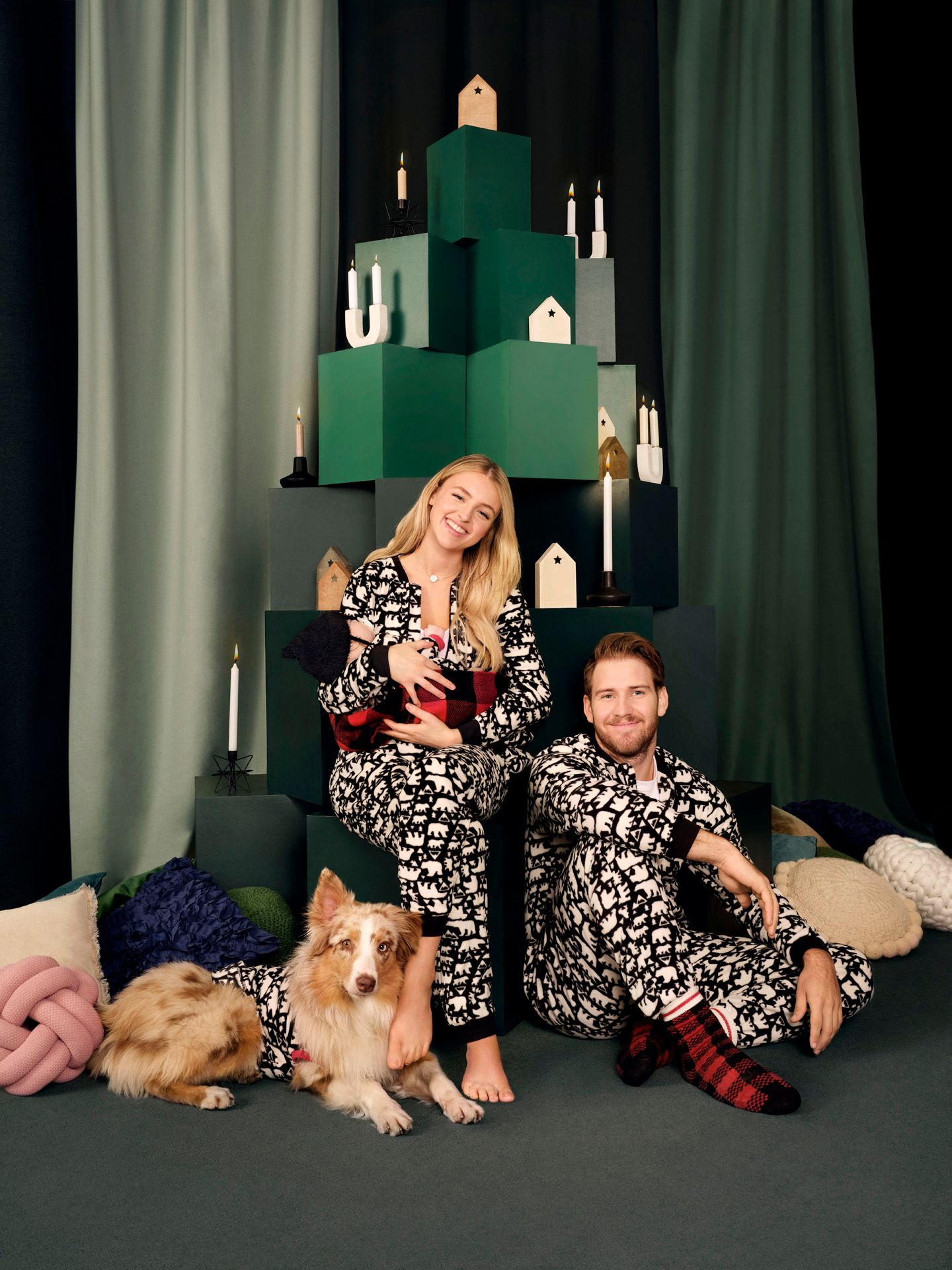 portrait of family of Alicia Moffatt in festive decor wearing matching pajamas with her husband newborn baby and dog for Aubainerie Christmas campaign about united family photographed and filmed by Maxyme G Delisle with artistic direction and set design by Studio TB