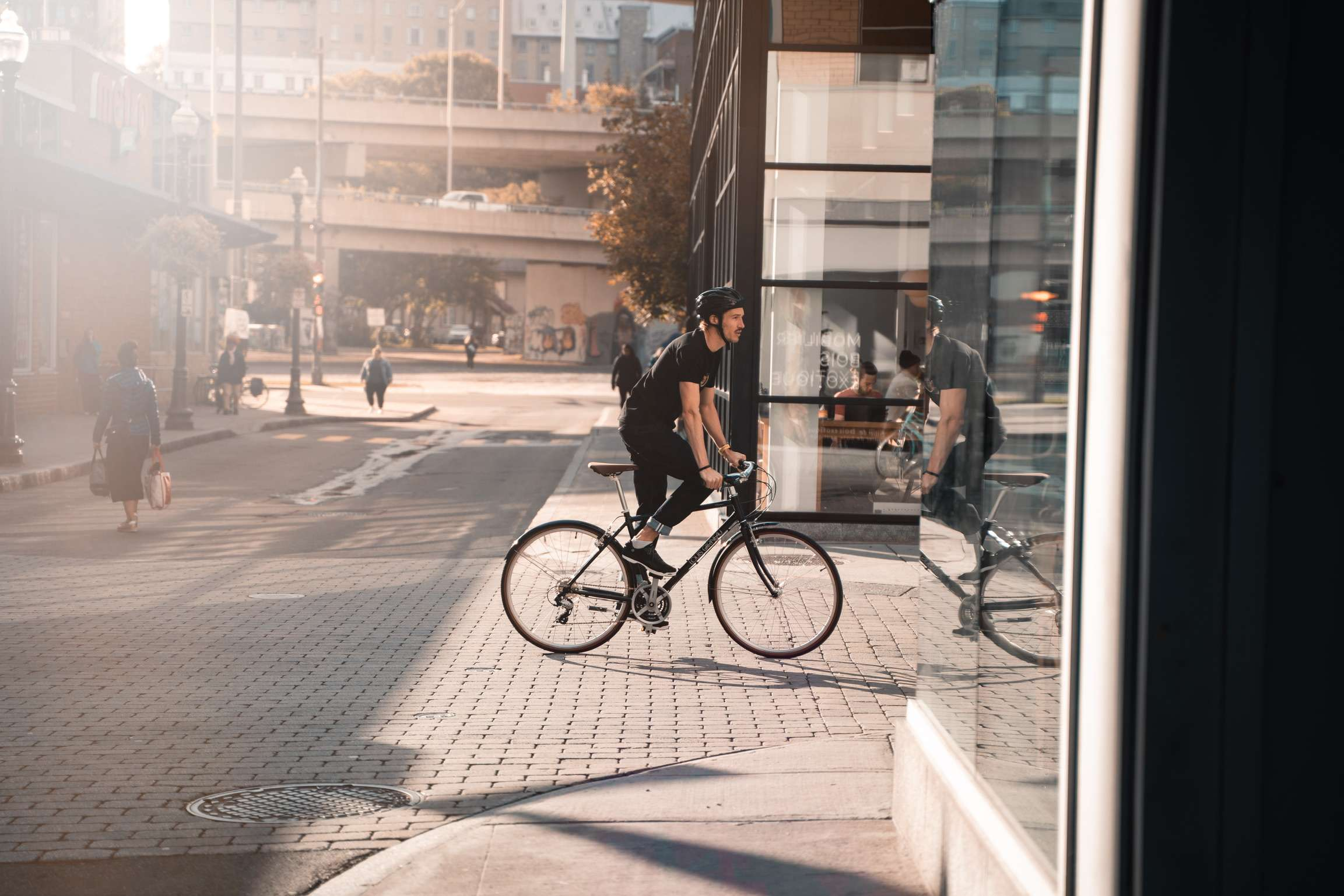 male model wearing black shirt with black jeans and black shoes biking in Montreal street on black bike in the sun as Spring Summer 2020 campaign of Louis Garneau with artistic direction and styling by Studio TB