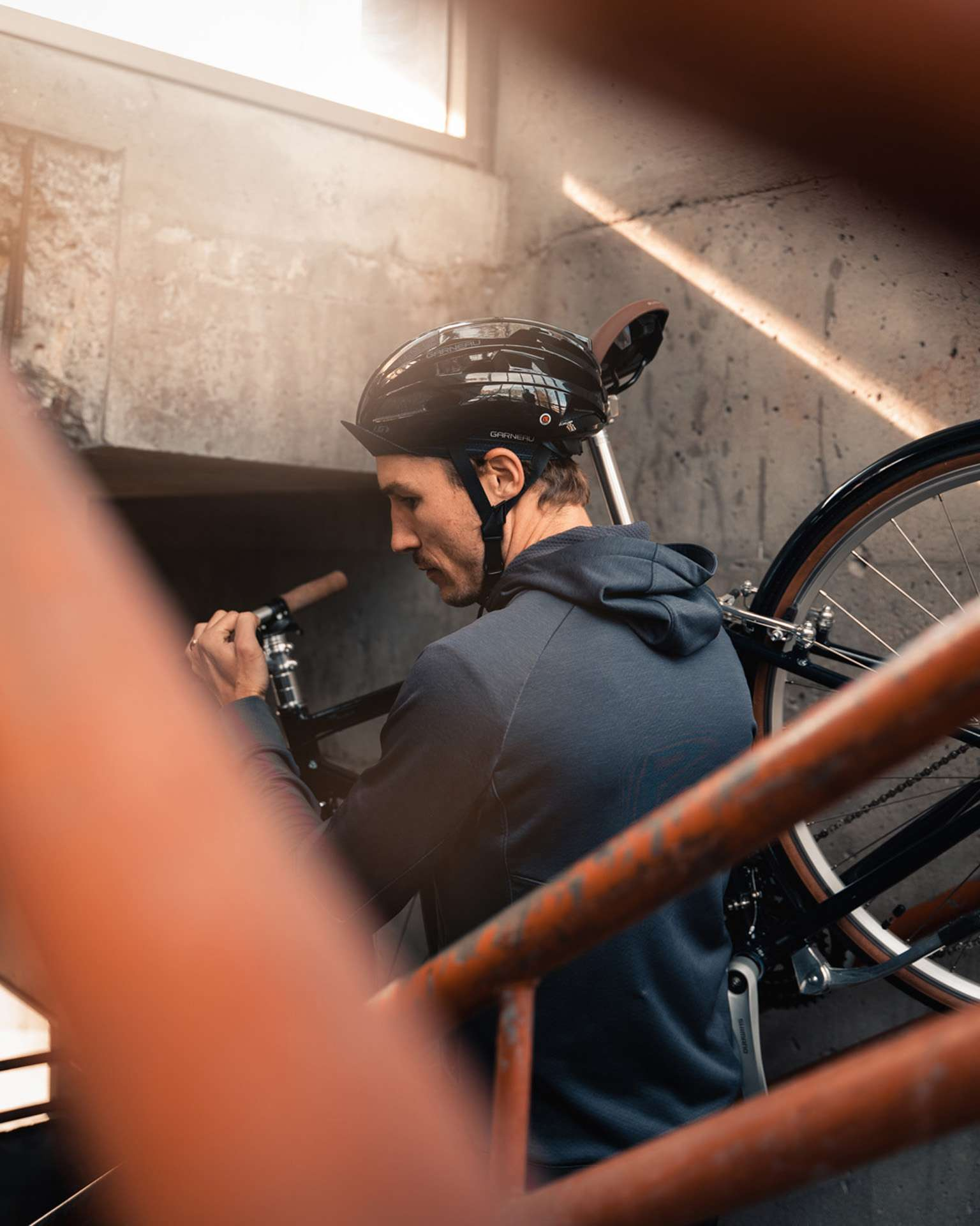 male model wearing bike helmet black shorts and dark blue jacket holding a bike over his shoulder while going down the stairs for Spring Summer 2020 campaign of Louis Garneau with artistic direction and styling by Studio TB