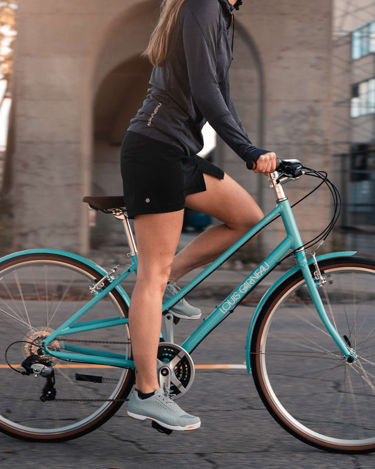 female model wearing black shorts grey jacket and grey shoes biking on turquoise bike for Spring Summer 2020 campaign of Louis Garneau with artistic direction and styling by Studio TB