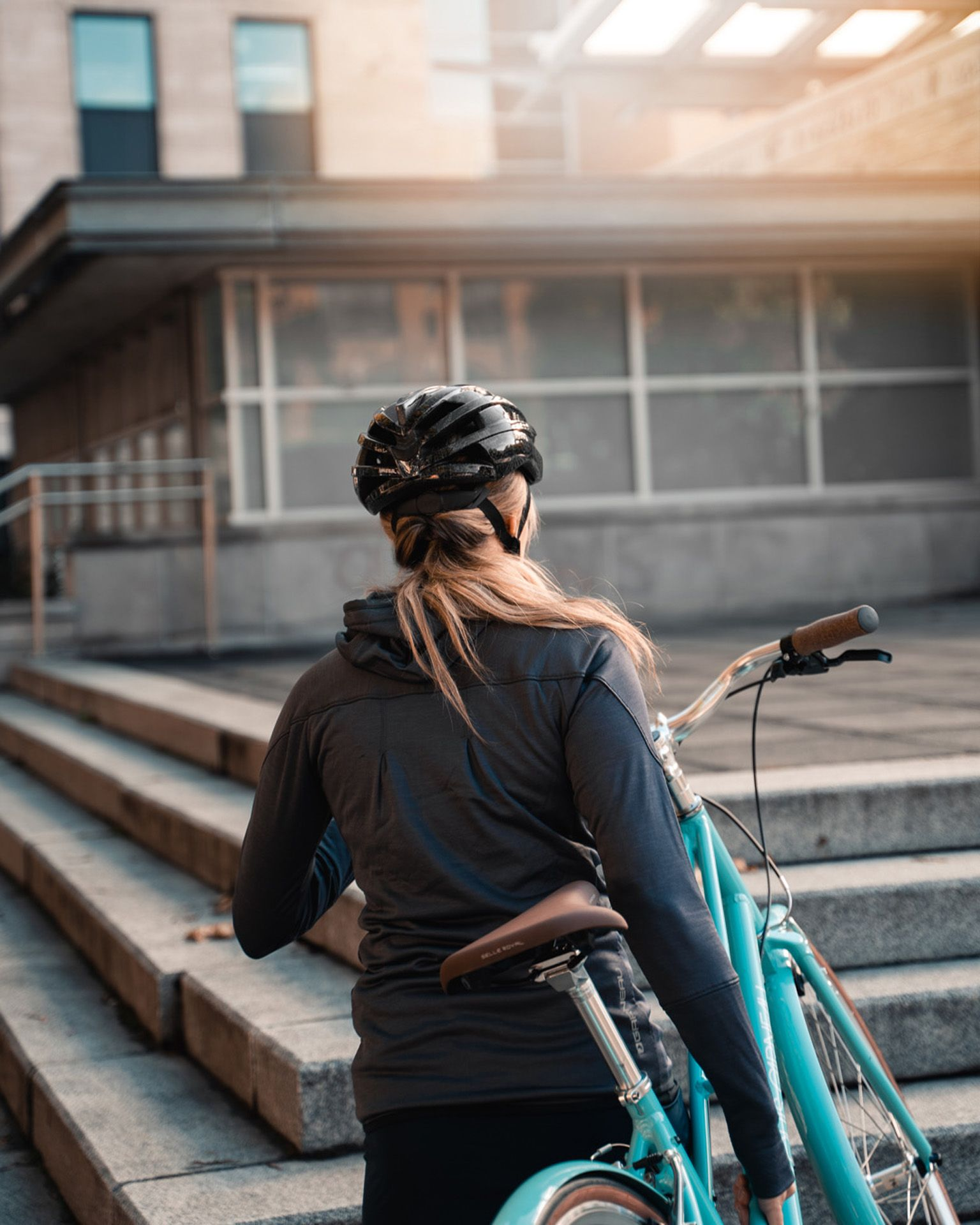 blonde female model wearing black bike helmet black shorts grey jacket and grey shoes hoisting up turquoise bike while walking up stairs for Spring Summer 2020 campaign of Louis Garneau with artistic direction and styling by Studio TB