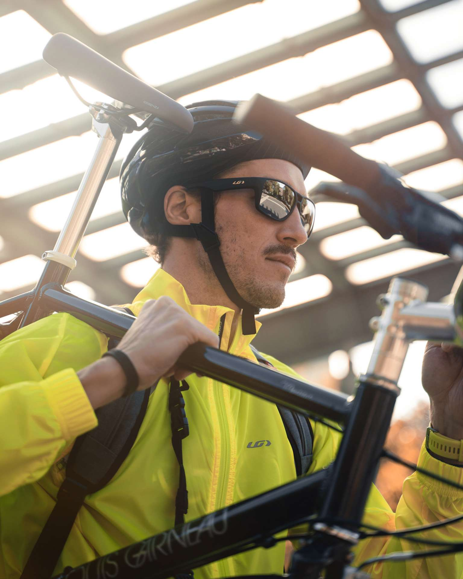male model wearing bike helmet with neon yellow jacket holding a bike over his shoulder for Spring Summer 2020 campaign of Louis Garneau with artistic direction and styling by Studio TB