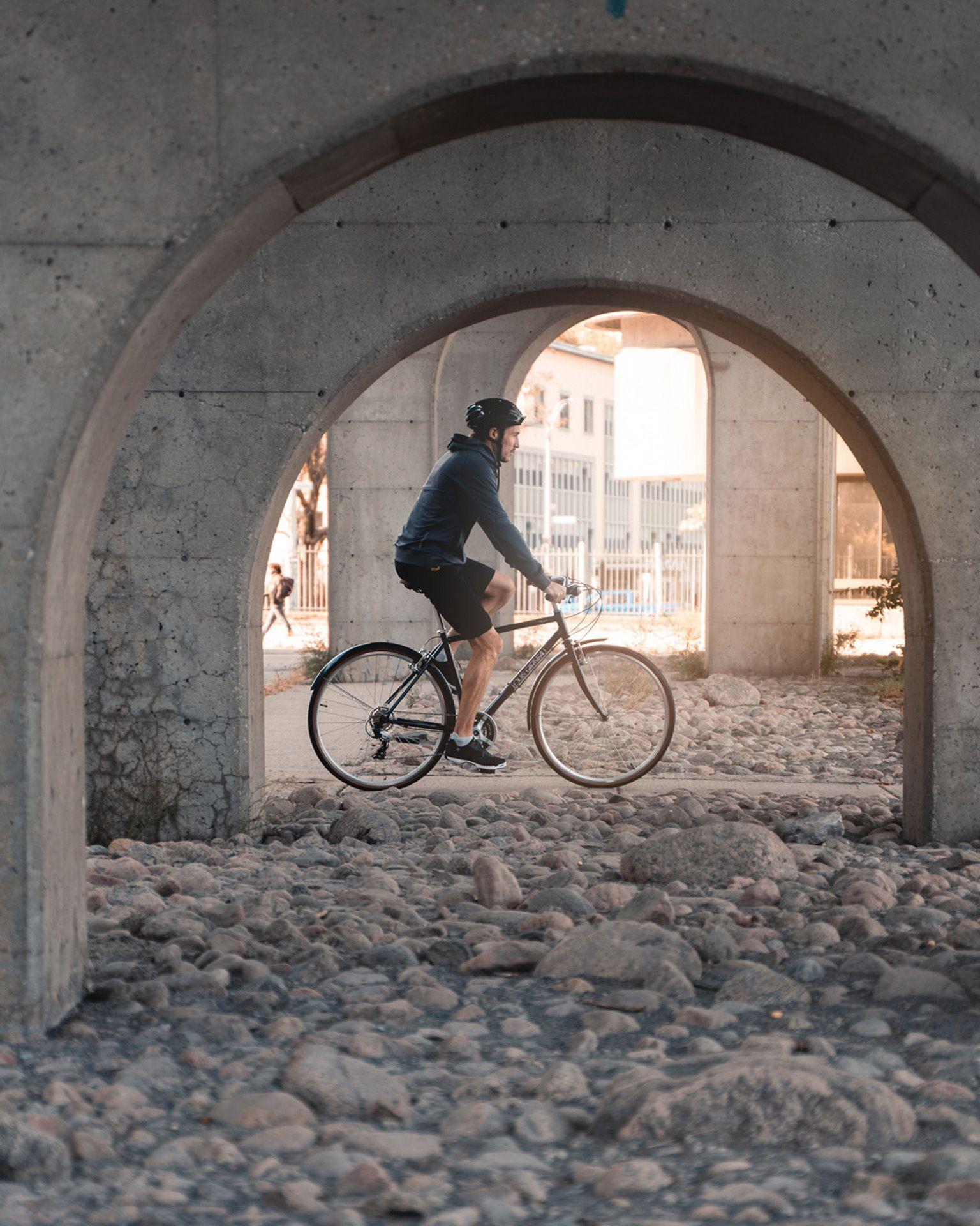 male model wearing bike helmet black shorts and dark blue jacket biking under a bridge on black bike as Spring Summer 2020 campaign of Louis Garneau with artistic direction and styling by Studio TB
