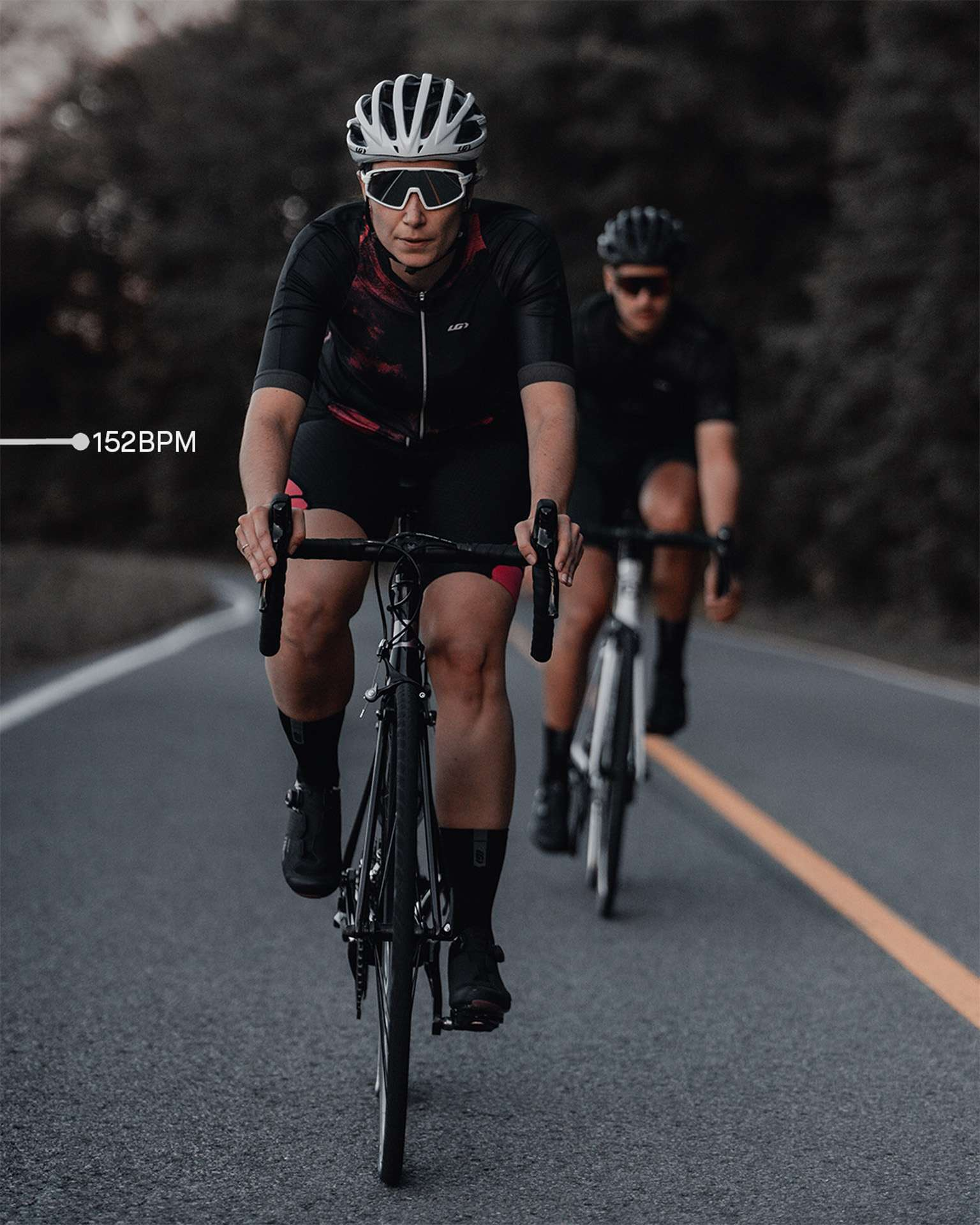 female model wearing black bike helmet and black and pink biking bodysuit with sunglasses biking on road on a black sports bike for Spring Summer 2020 campaign of Louis Garneau with artistic direction and styling by Studio TB