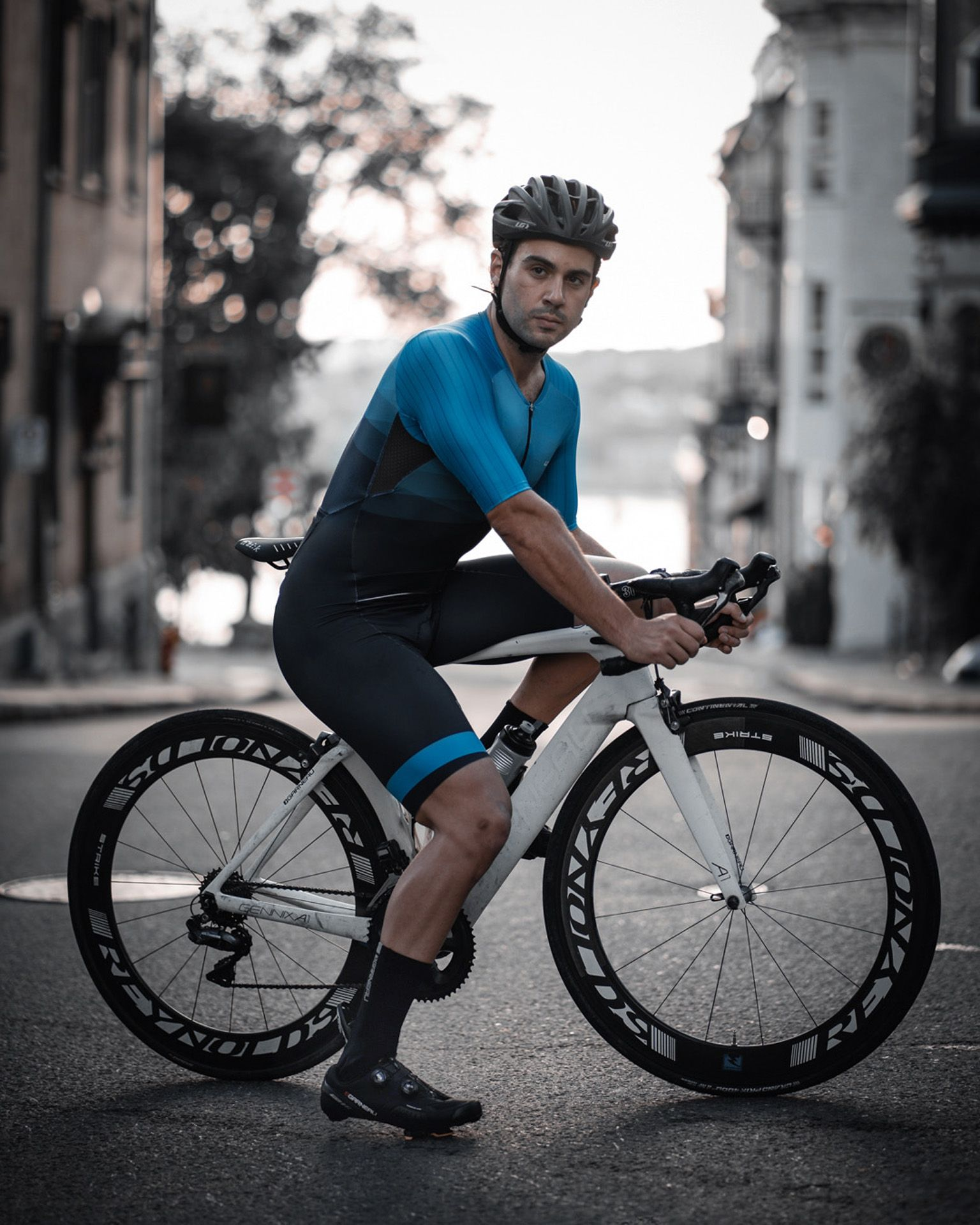 male model wearing black bike helmet and black and blue biking bodysuit sitting on a white sports bike for Spring Summer 2020 campaign of Louis Garneau with artistic direction and styling by Studio TB