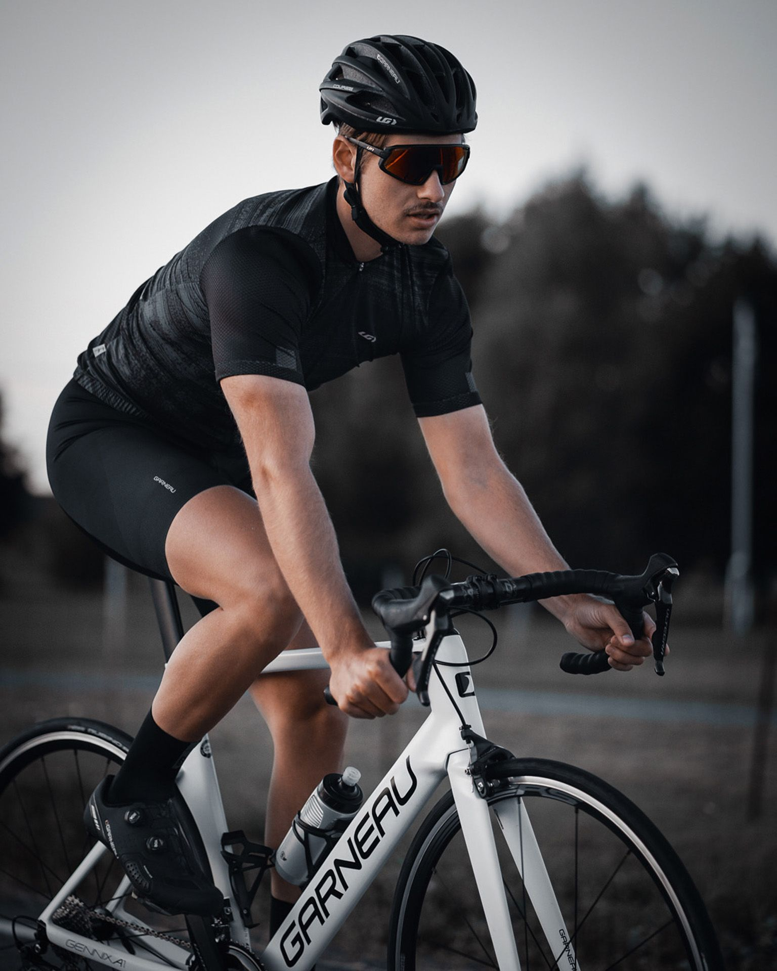 male model wearing black bike helmet and black biking bodysuit with sunglasses biking on road on a white sports bike for Spring Summer 2020 campaign of Louis Garneau with artistic direction and styling by Studio TB