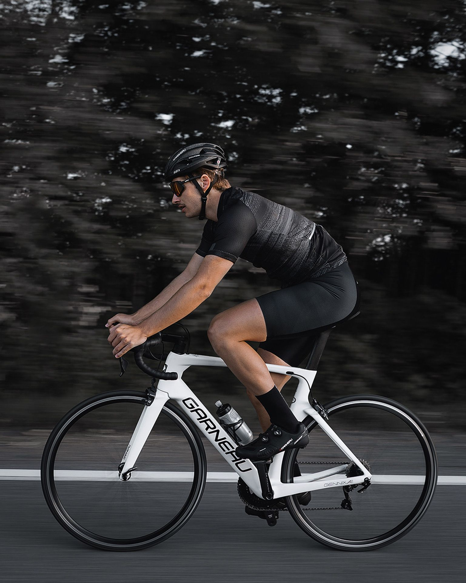 male model wearing black bike helmet and black biking bodysuit with sunglasses biking fast on road on a white sports bike for Spring Summer 2020 campaign of Louis Garneau with artistic direction and styling by Studio TB