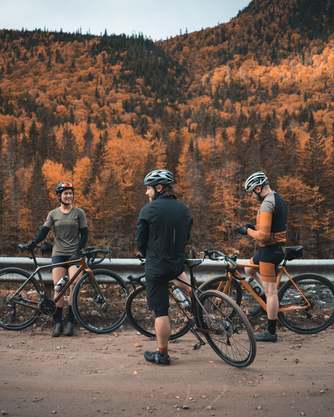 trio of long distance bikers talking on side of the road with mountains covered in orange colored trees in the background for Spring Summer 2020 campaign of Louis Garneau with artistic direction and styling by Studio TB
