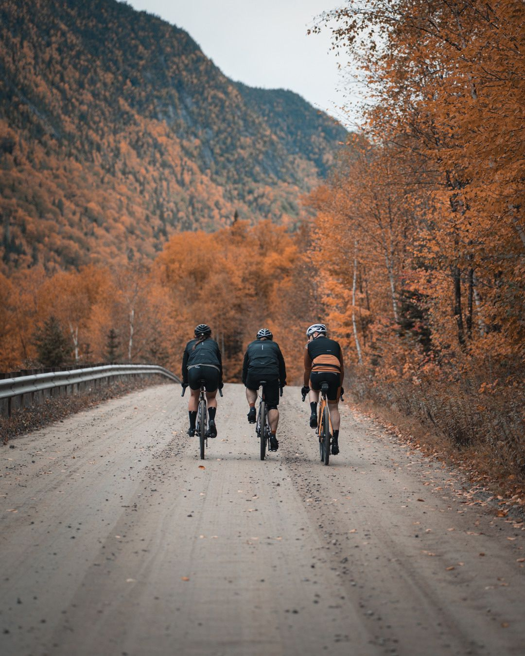 trio of long distance bikers biking on dirt road side by side with mountains covered in orange colored trees in the background for Spring Summer 2020 campaign of Louis Garneau with artistic direction and styling by Studio TB
