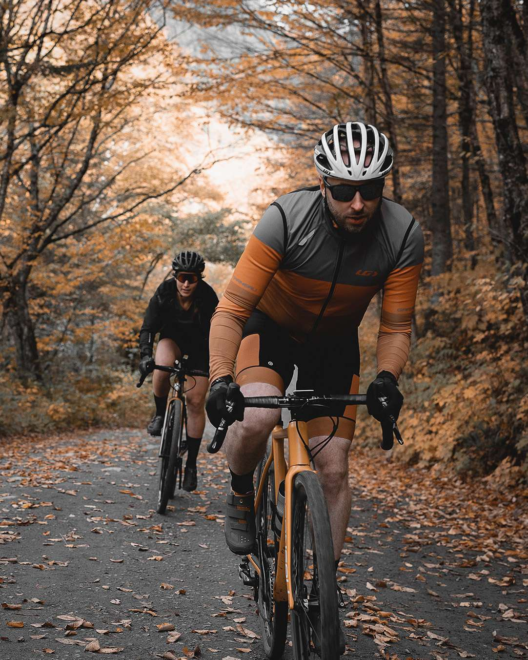trio of long distance bikers biking on dirt road one behind the other with mountains covered in orange colored trees in the background for Spring Summer 2020 campaign of Louis Garneau with artistic direction and styling by Studio TB