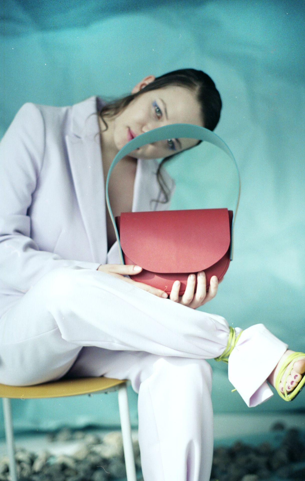 female model sitting on chair wearing light pastel pink suit jacket and pants holding small hot pink leather bag with light blue strap with light blue background for bouquet Montreal-brand Spring-Summer 2020 campaign with styling and artistic direction by Studio TB