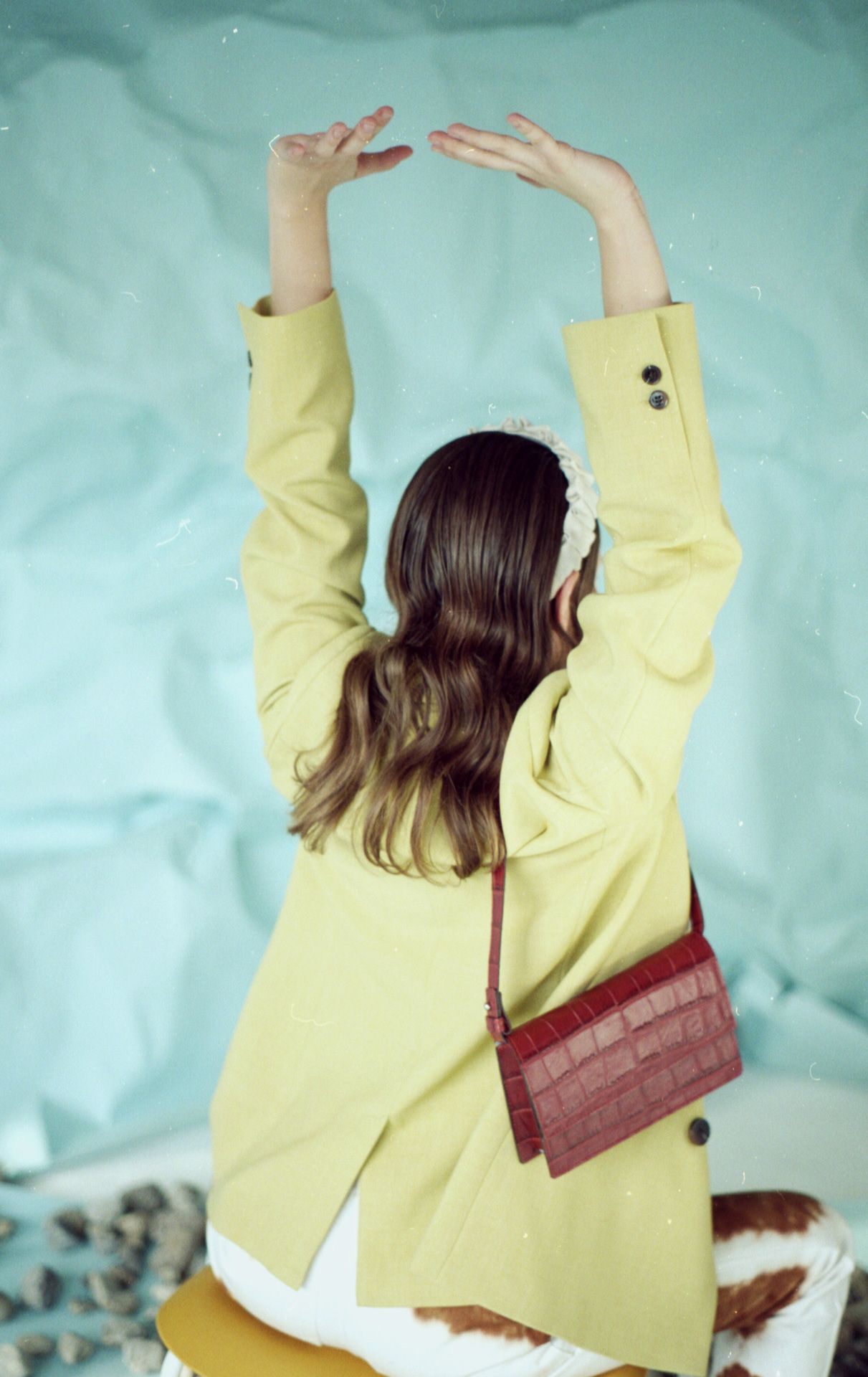 female model sitting on chair wearing light green suit jacket and cow patterned pants arms in the air and a small dark red shoulder bag on light blue background for bouquet Montreal-brand Spring-Summer 2020 campaign with styling and artistic direction by Studio TB