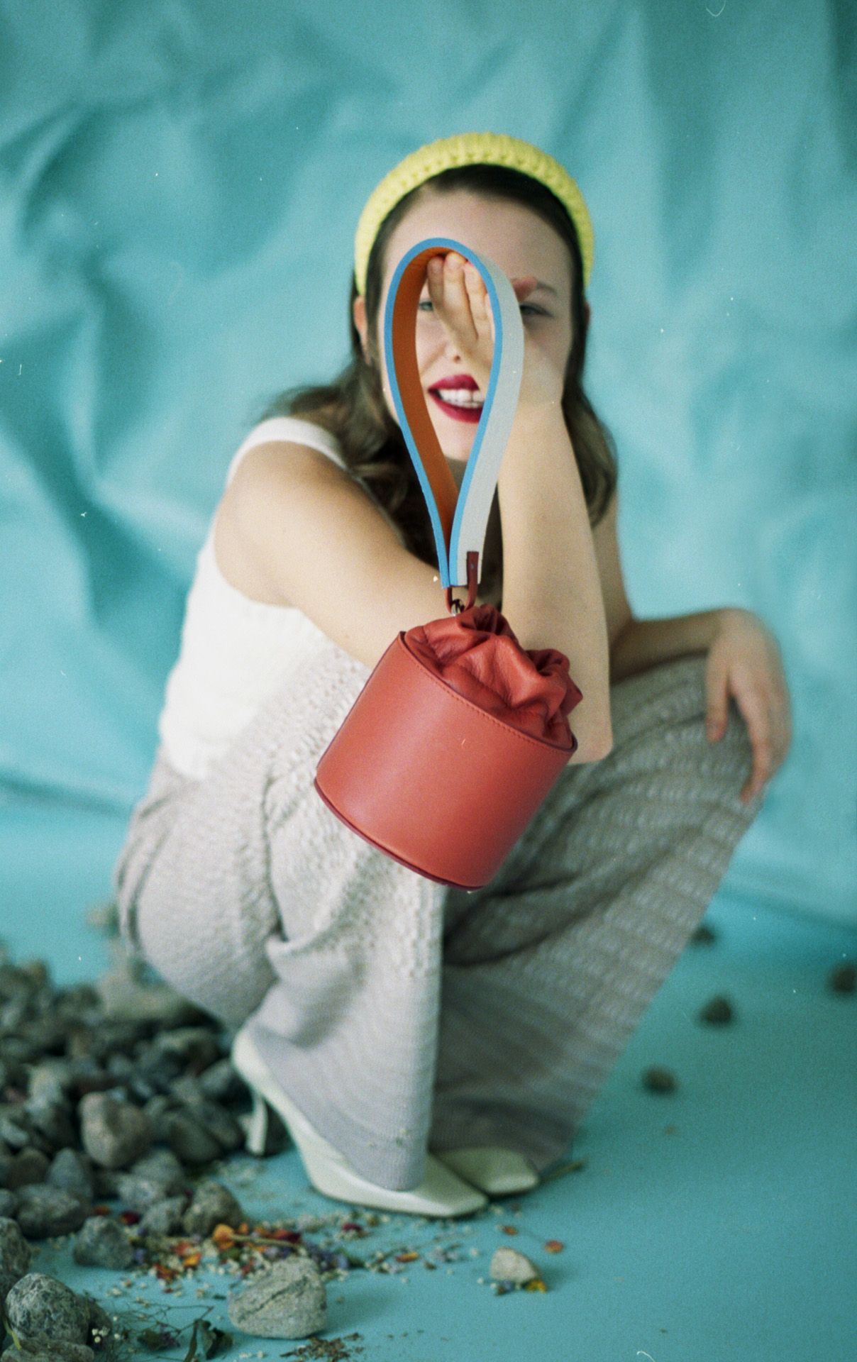 female model wearing crocheted white top with grey pants and white heels holding tube red leather bag by it's large white stripe in front of her face on light blue background for bouquet Montreal-brand Spring-Summer 2020 campaign with styling and artistic direction by Studio TB