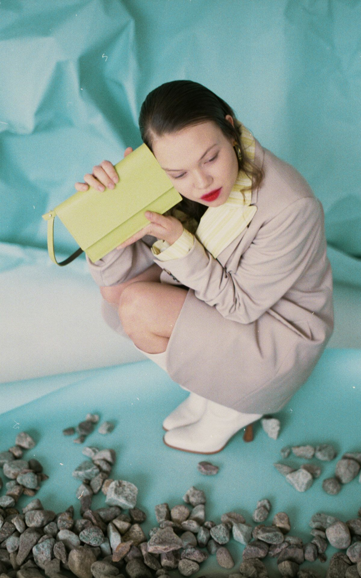 female model crouching on the ground surrounded by rocks wearing long beige coat and white heeled boots holding small light green leather bag against her face with light blue background for bouquet Montreal-brand Spring-Summer 2020 campaign with styling and artistic direction by Studio TB