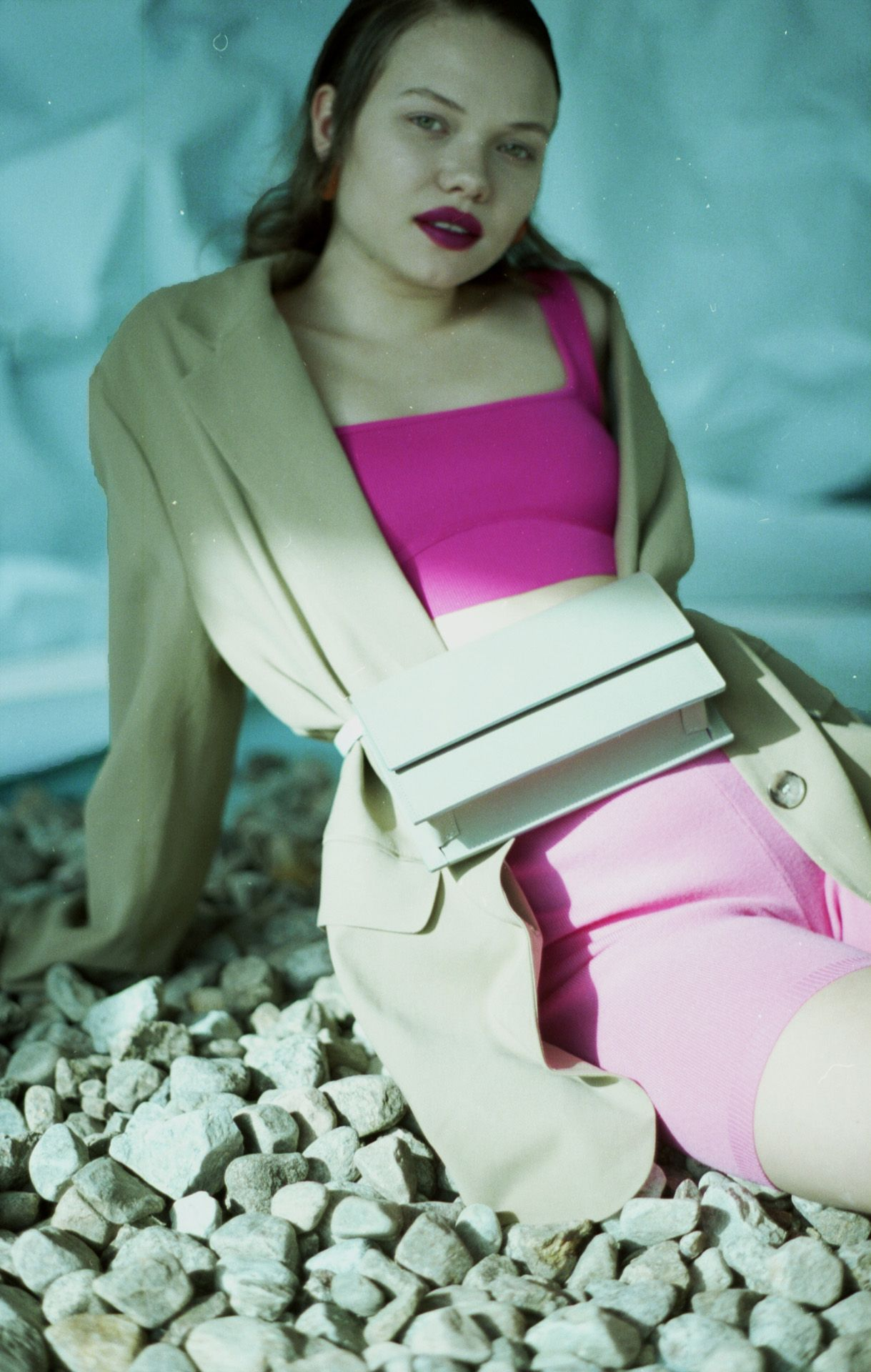 female model sitting on rocks wearing large beige coat with hot pink biker shorts and sports bra and light blue leather bag on light blue background for bouquet Montreal-brand Spring-Summer 2020 campaign with styling and artistic direction by Studio TB