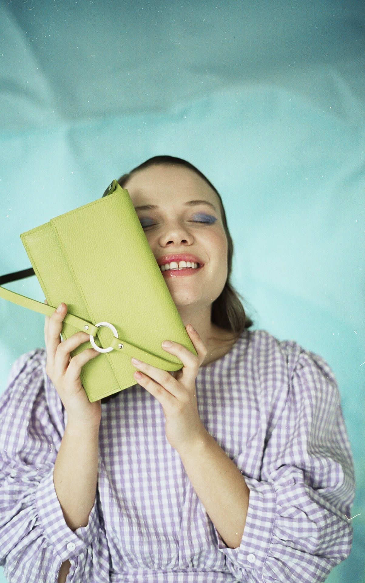 female model wearing purple and white checkered top smiling and holding light green leather purse against her face on light blue background for bouquet Montreal-brand Spring-Summer 2020 campaign with styling and artistic direction by Studio TB
