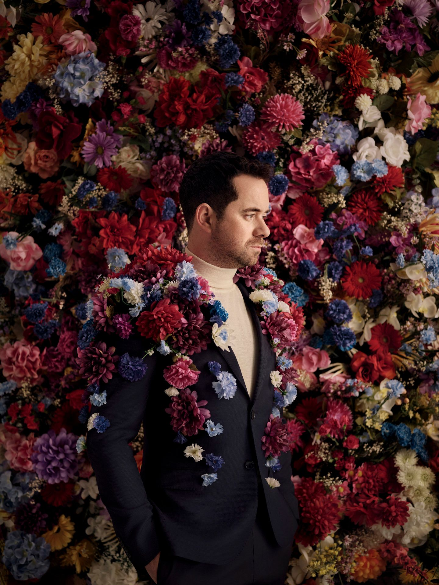 singer Jean-Michel Blais wearing suit jacket covered in fake flowers with fake flower covered wall in the background photographed by Maxyme G Delisle with artistic direction and styling by Studio TB