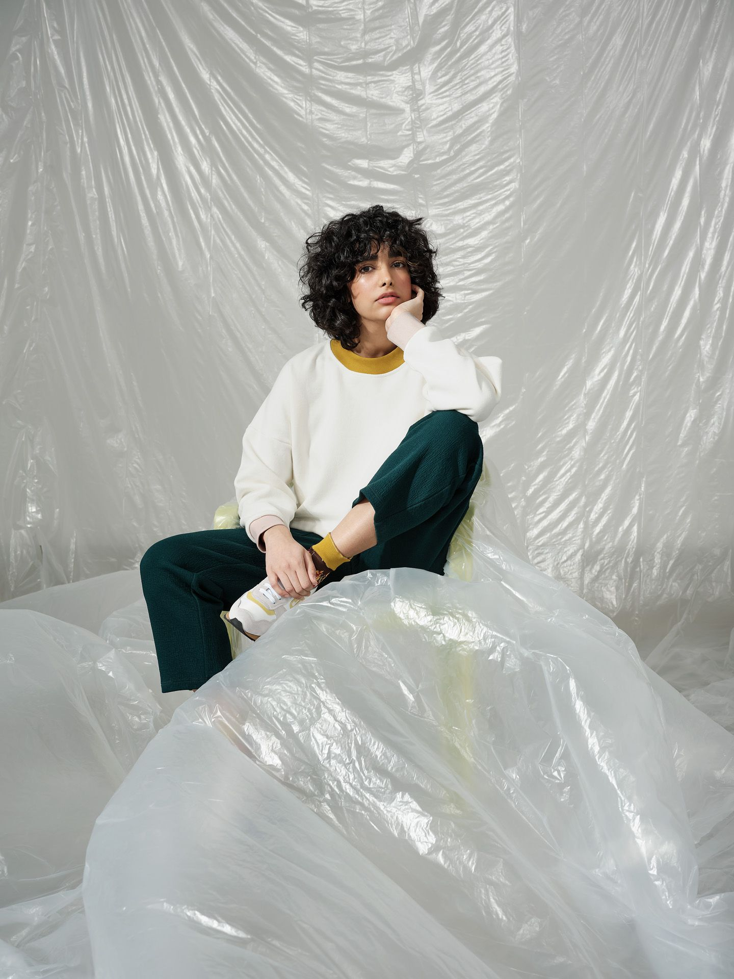 curly haired female model wearing white sweater with mustard collar and dark green pants sitting on green plastic chair covered in plastic construction sheet looking at camera photographed by Maxyme G Delisle with artistic direction and styling by Studio TB