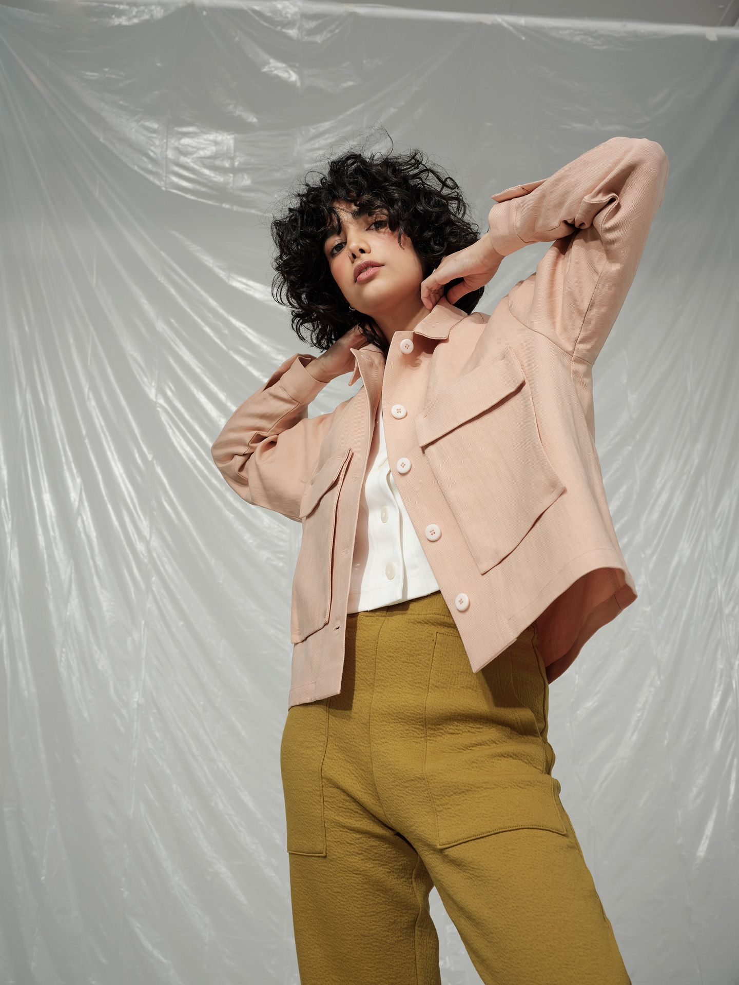 curly haired female model wearing soft pink jacket white tee shirt and mustard pants posing with arms up in the air looking at camera photographed by Maxyme G Delisle with artistic direction and styling by Studio TB