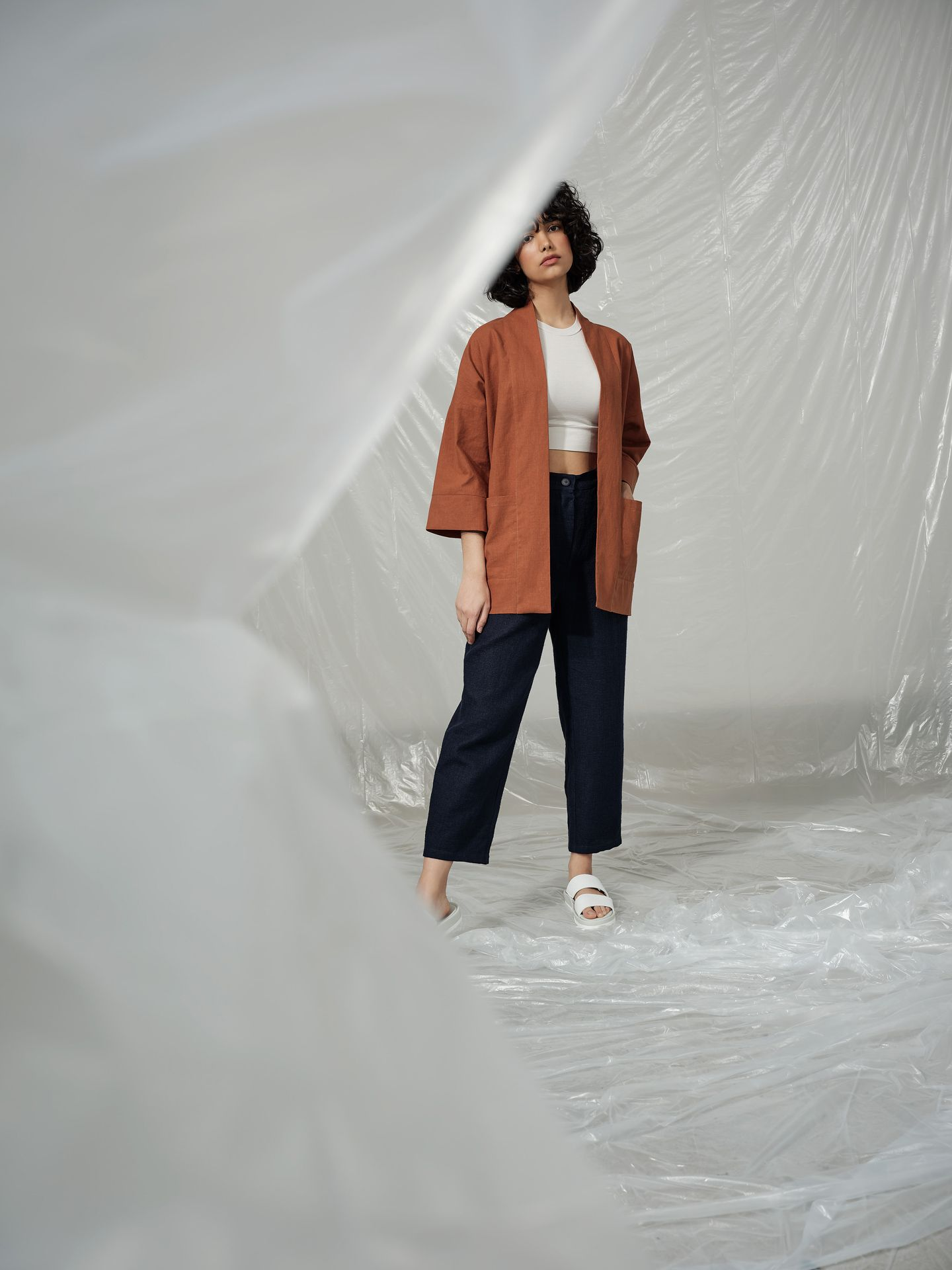 curly haired female model wearing brown jacket tight white crop top and baggy dark blue pants standing in room covered in plastic construction sheet looking at camera photographed by Maxyme G Delisle with artistic direction and styling by Studio TB