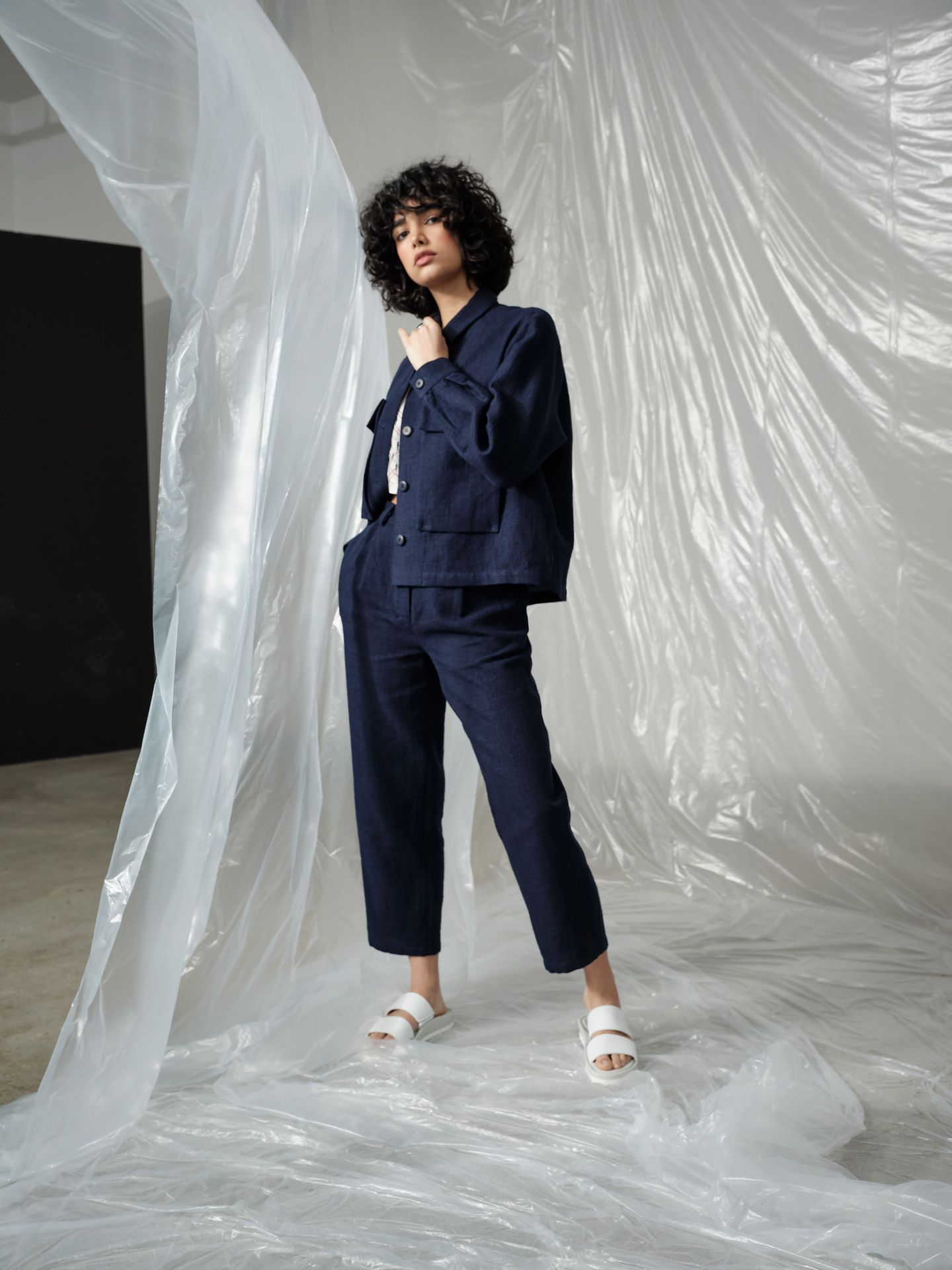 curly haired female model wearing dark blue linen ensemble standing looking at camera photographed by Maxyme G Delisle with artistic direction and styling by Studio TB