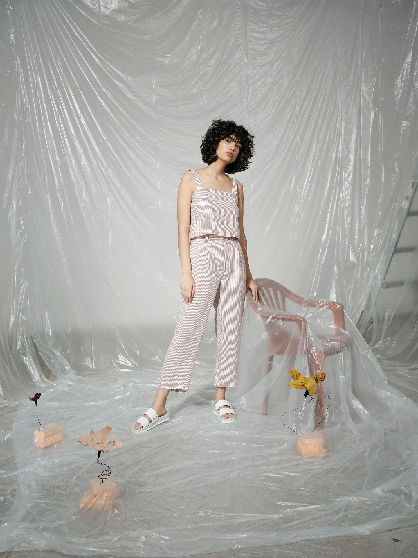 curly haired female model wearing soft pink and white stripped ensemble standing next to pink plastic chair covered in plastic construction sheet looking at camera photographed by Maxyme G Delisle with artistic direction and styling by Studio TB