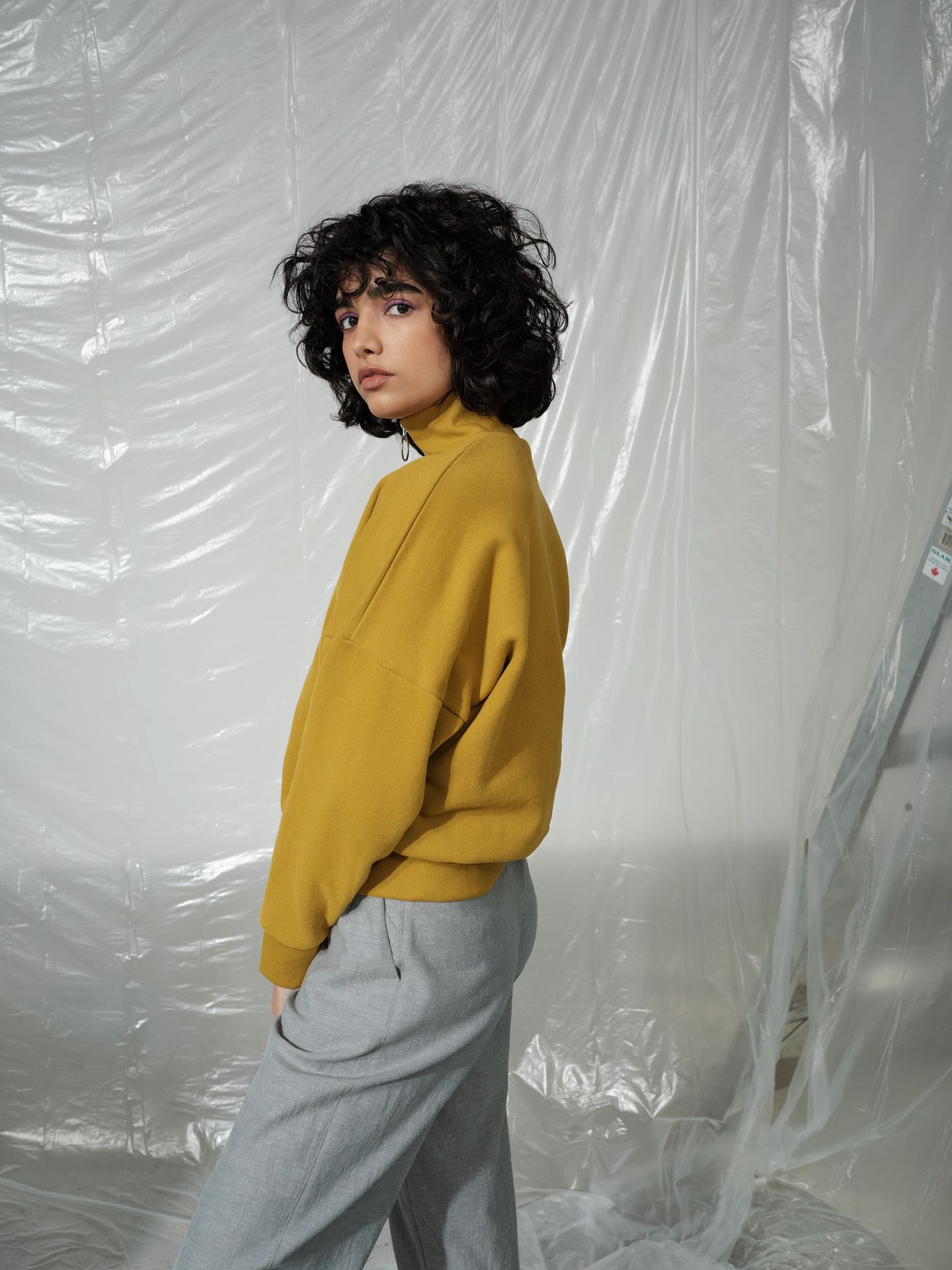 curly haired female model wearing mustard sweater and grey pants posing looking at camera photographed by Maxyme G Delisle with artistic direction and styling by Studio TB