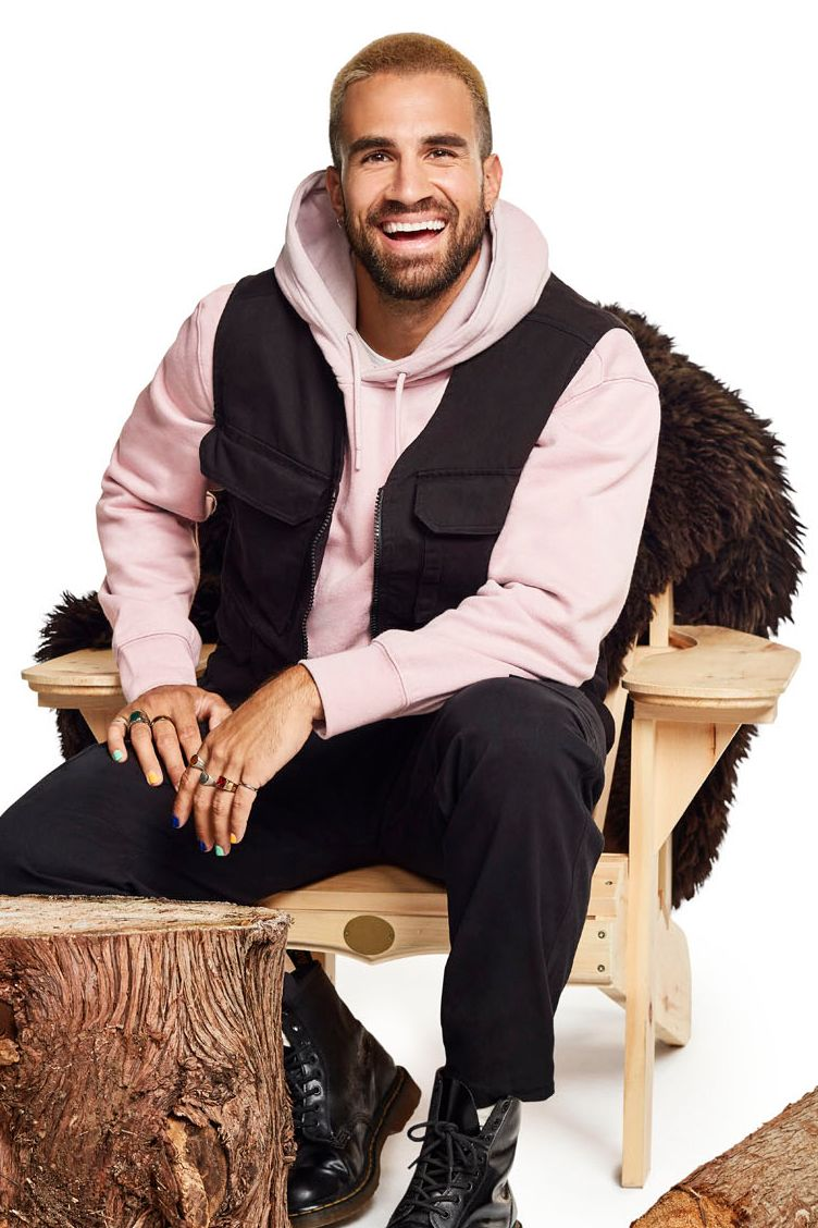 reality TV show Occupation Double host Jay Du Temple sitting on wooden chair smiling photographed by Jocelyn Michel for Noovo Bell Media