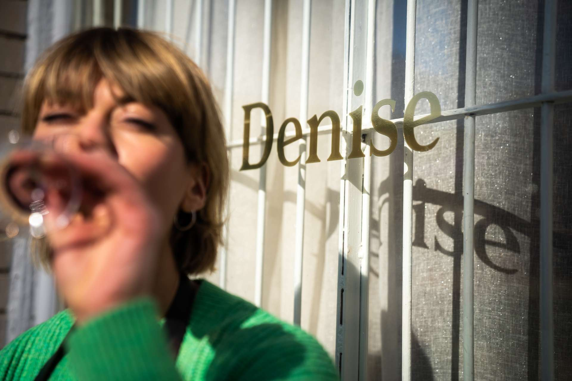 Dahls workwear and aprons photographed by Bruno Florin of woman drinking glass of wine in front of Denise boutique