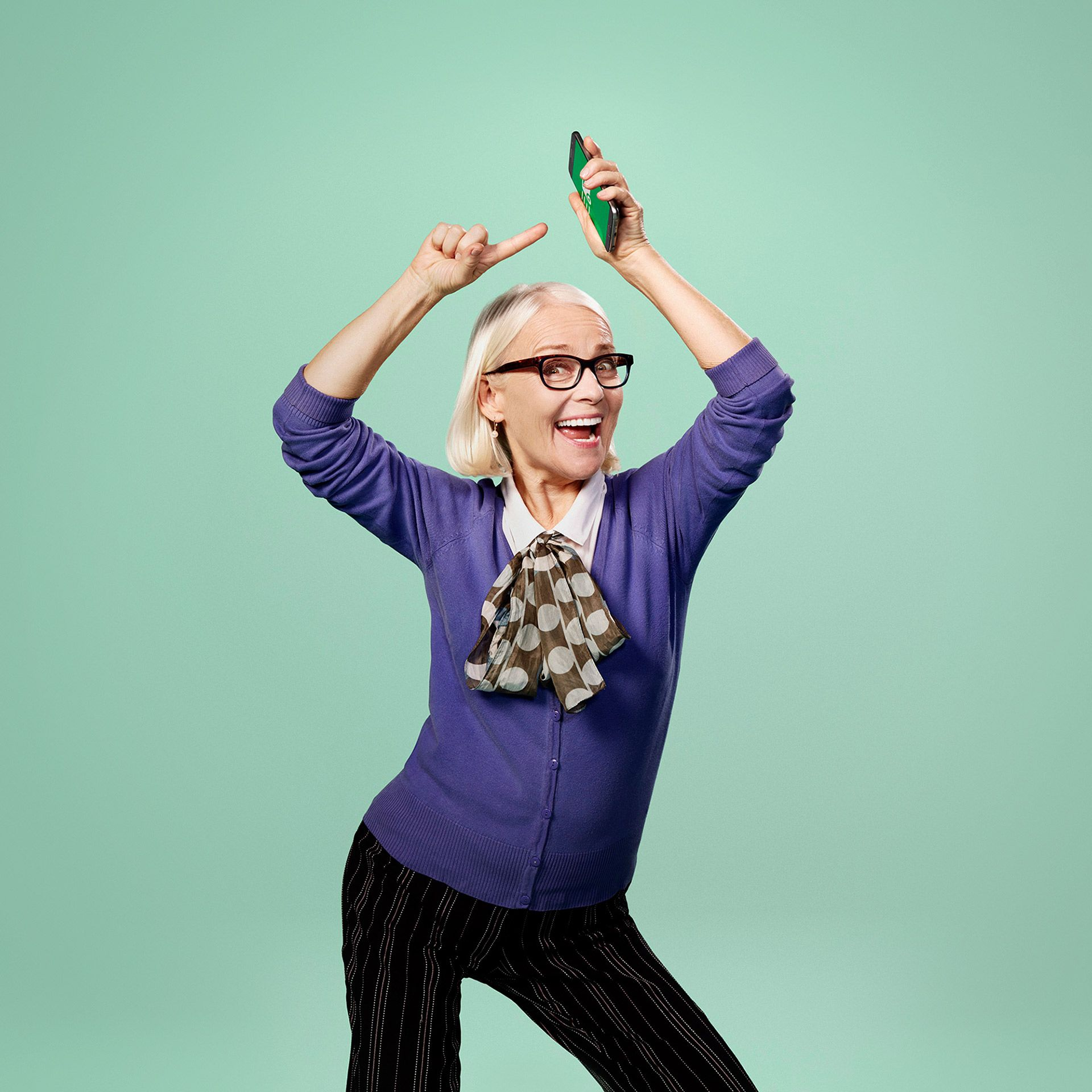 old lady in purple cardigan happy dancing pointing at phone over her head by Jocelyn Michel for Desjardins Assurance with Lg2