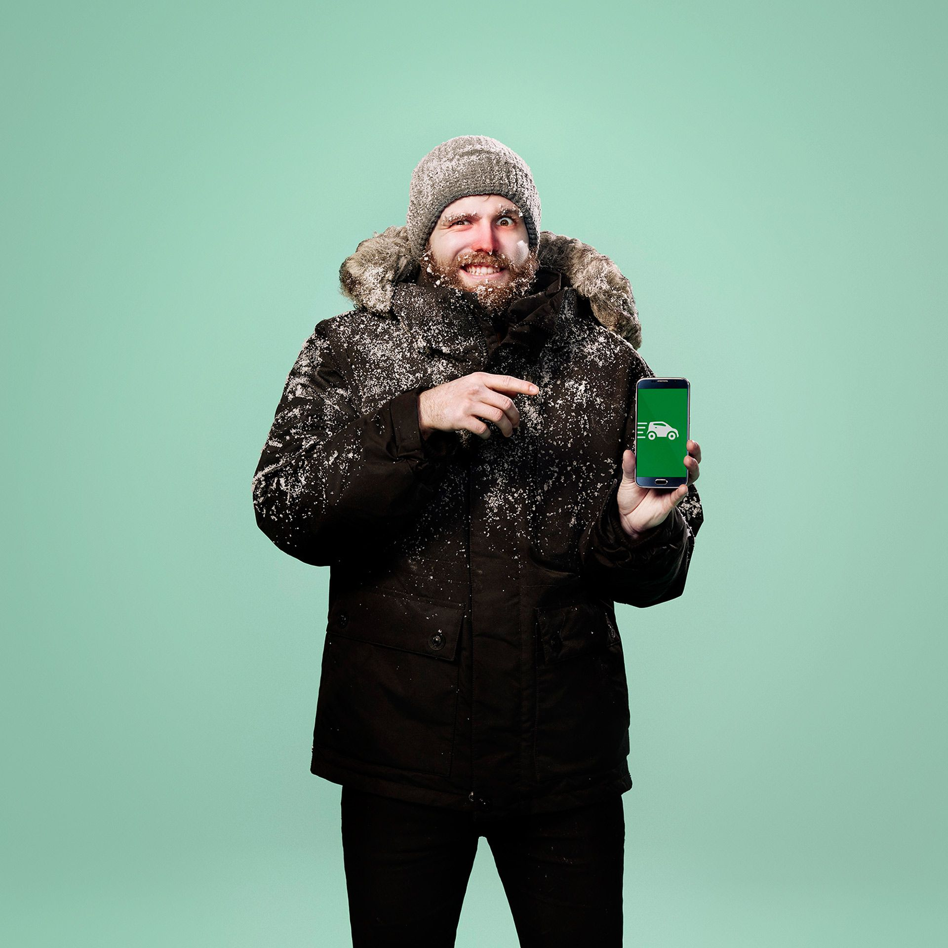 man dressed in winter gear covered in snow red nosed pointing at phone by Jocelyn Michel for Desjardins Assurance with Lg2