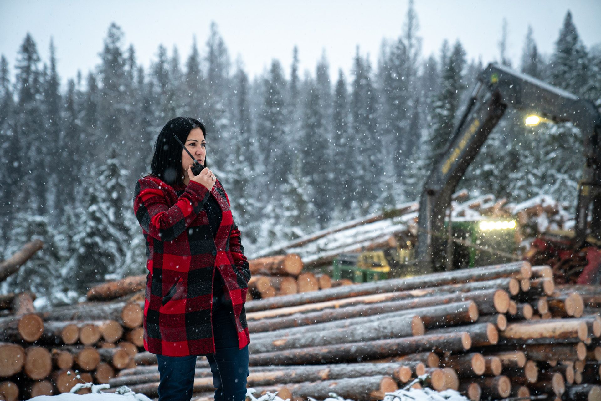 woman in plaid coat talking in a walkie talkie among cut trees by Bruno Florin for BDC Beyond Business with Cossette