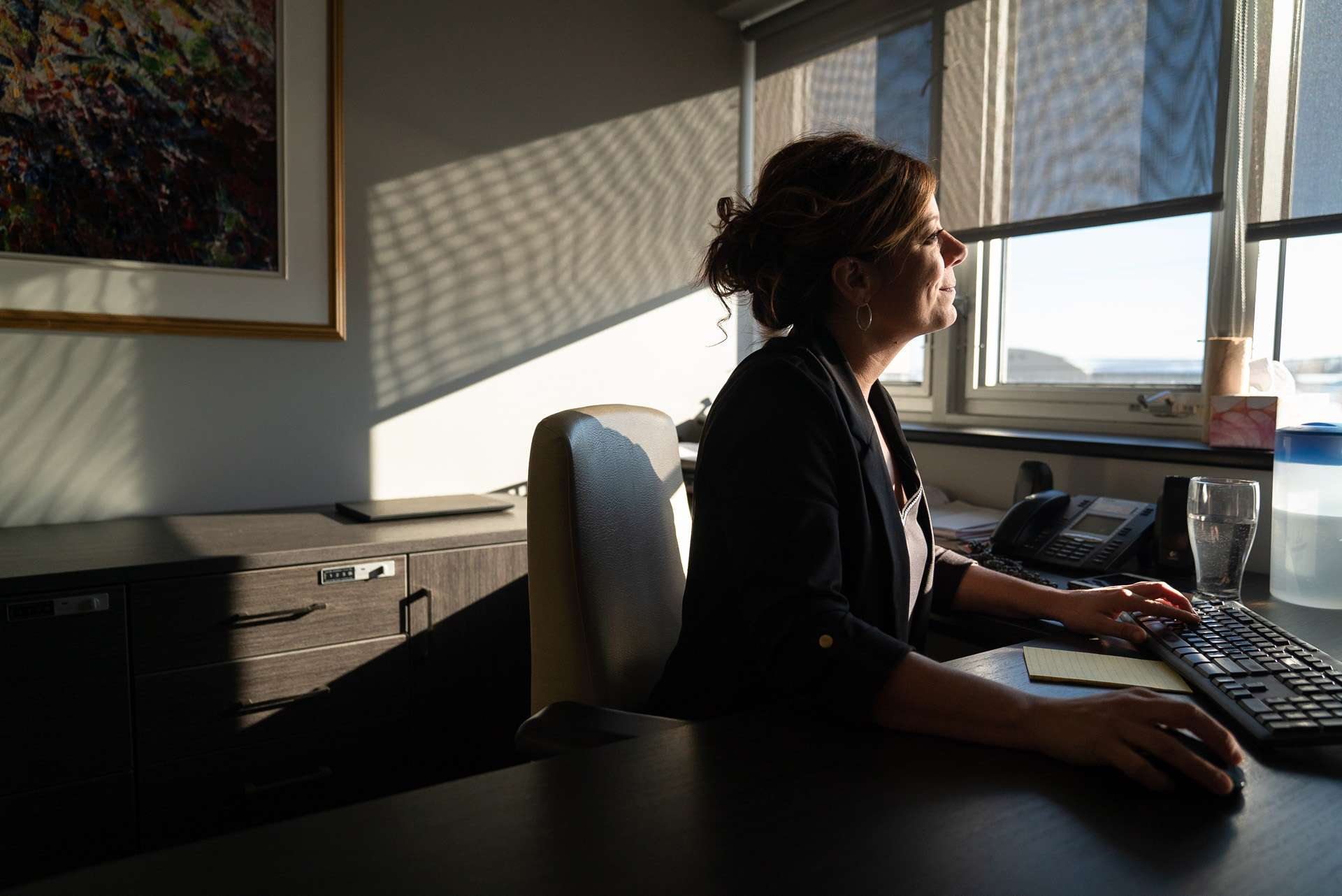 woman working in office looking at computer face in the sun smiling by Bruno Florin for BDC Beyond Business with Cossette