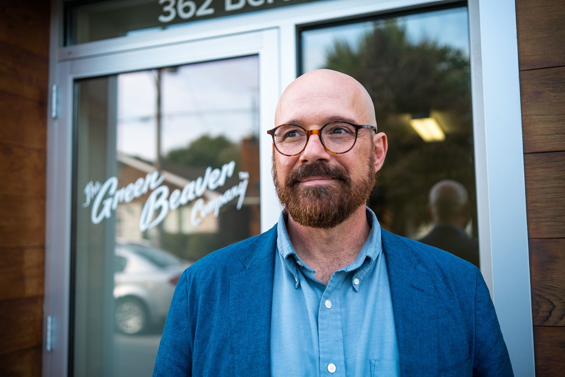 bald man in front of Green Beaver Company wearing blue blazer glasses and beard by Bruno Florin for BDC Beyond Business with Cossette