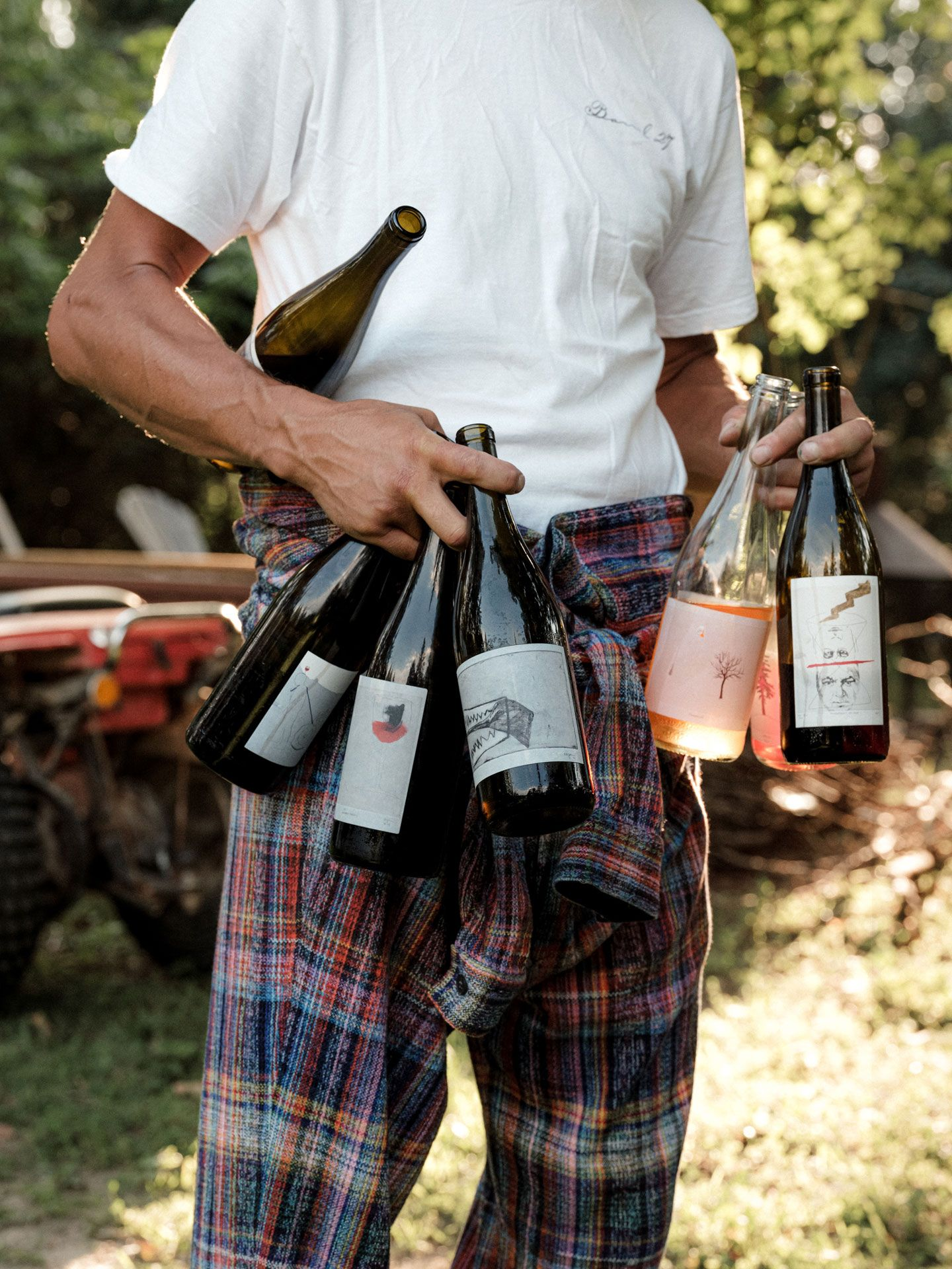 winemaker from Pinard & Filles holding seven bottles of wine in his arms and hands by Alexi Hobbs for Larose Paris