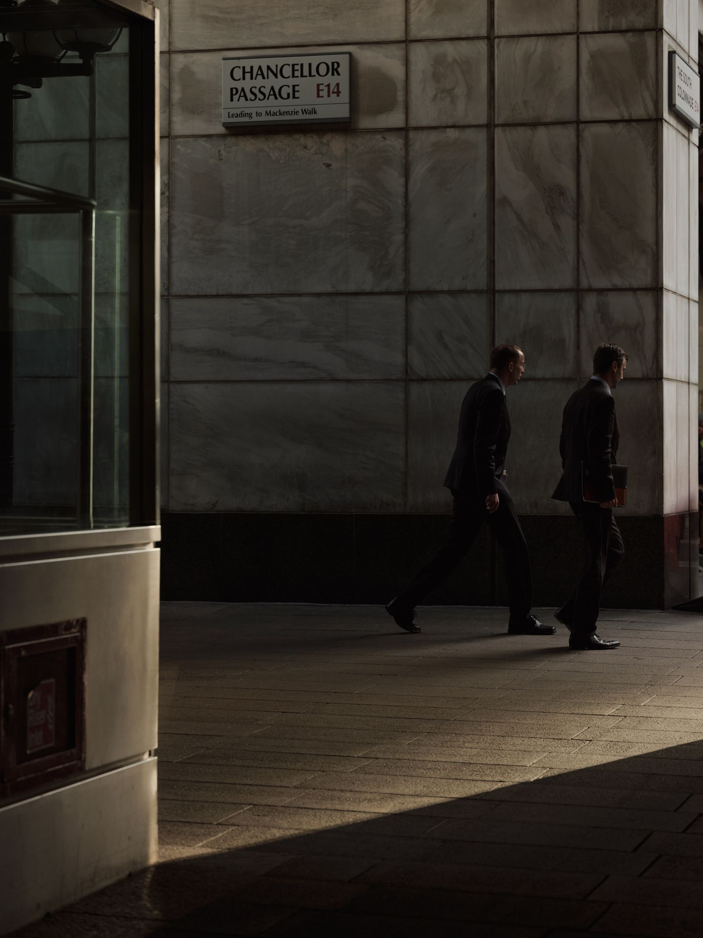 two man wearing professional suit walking out of building in ray of sun for PSP by Alexi Hobbs