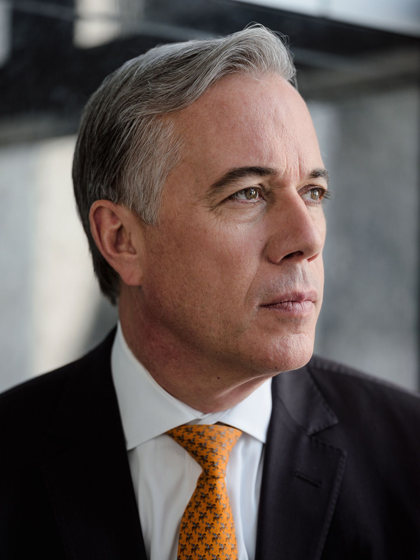 middle aged man with grey hair and light blue eyes wearing professional suit with orange tie looking out the window photographed by Alexi Hobbs for PSP
